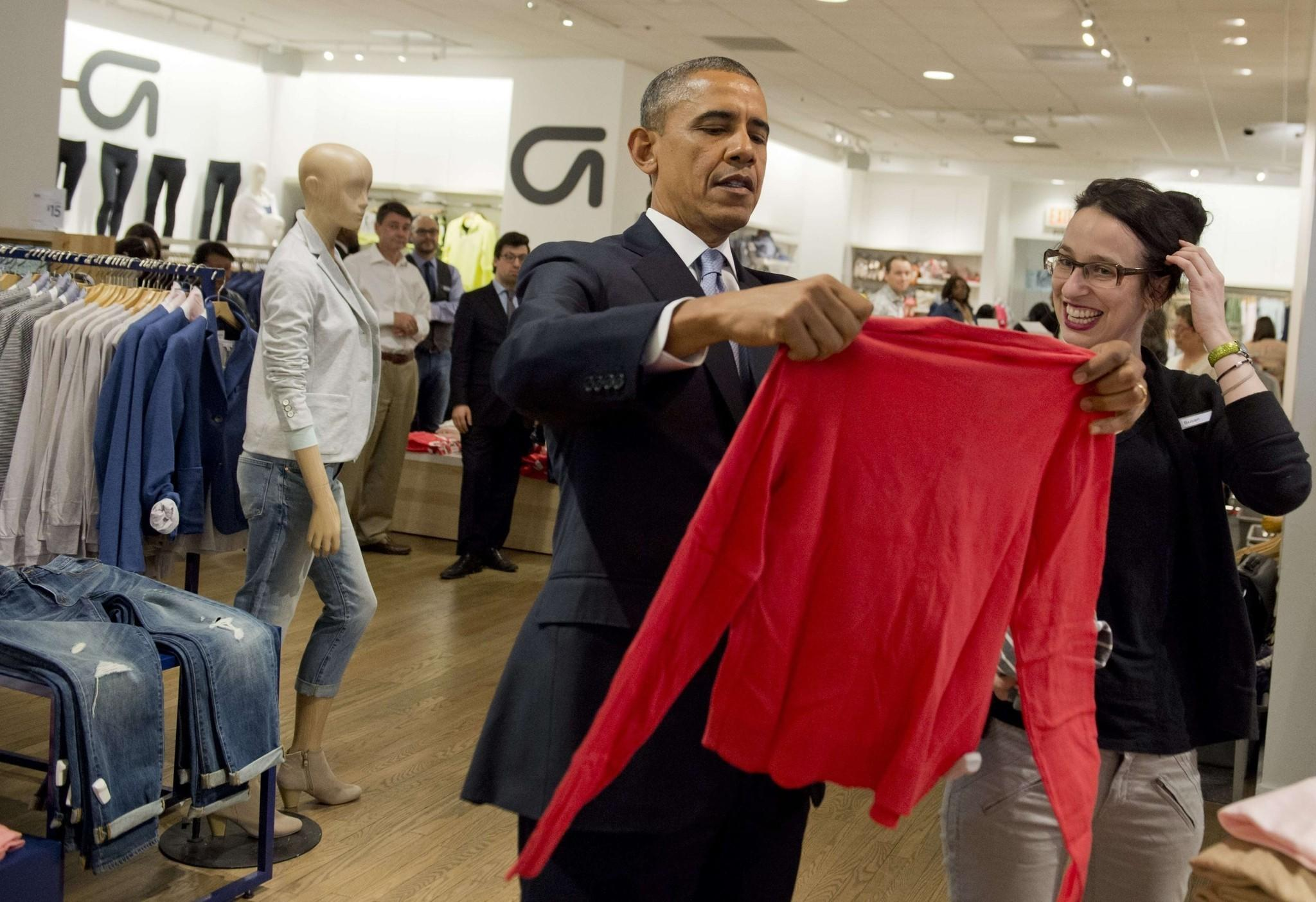 President Obama shops for clothing for his family alongside store employee Susan Panariello during a visit to a Gap clothing store in New York City to highlight his proposal to raise the federal minimum wage.