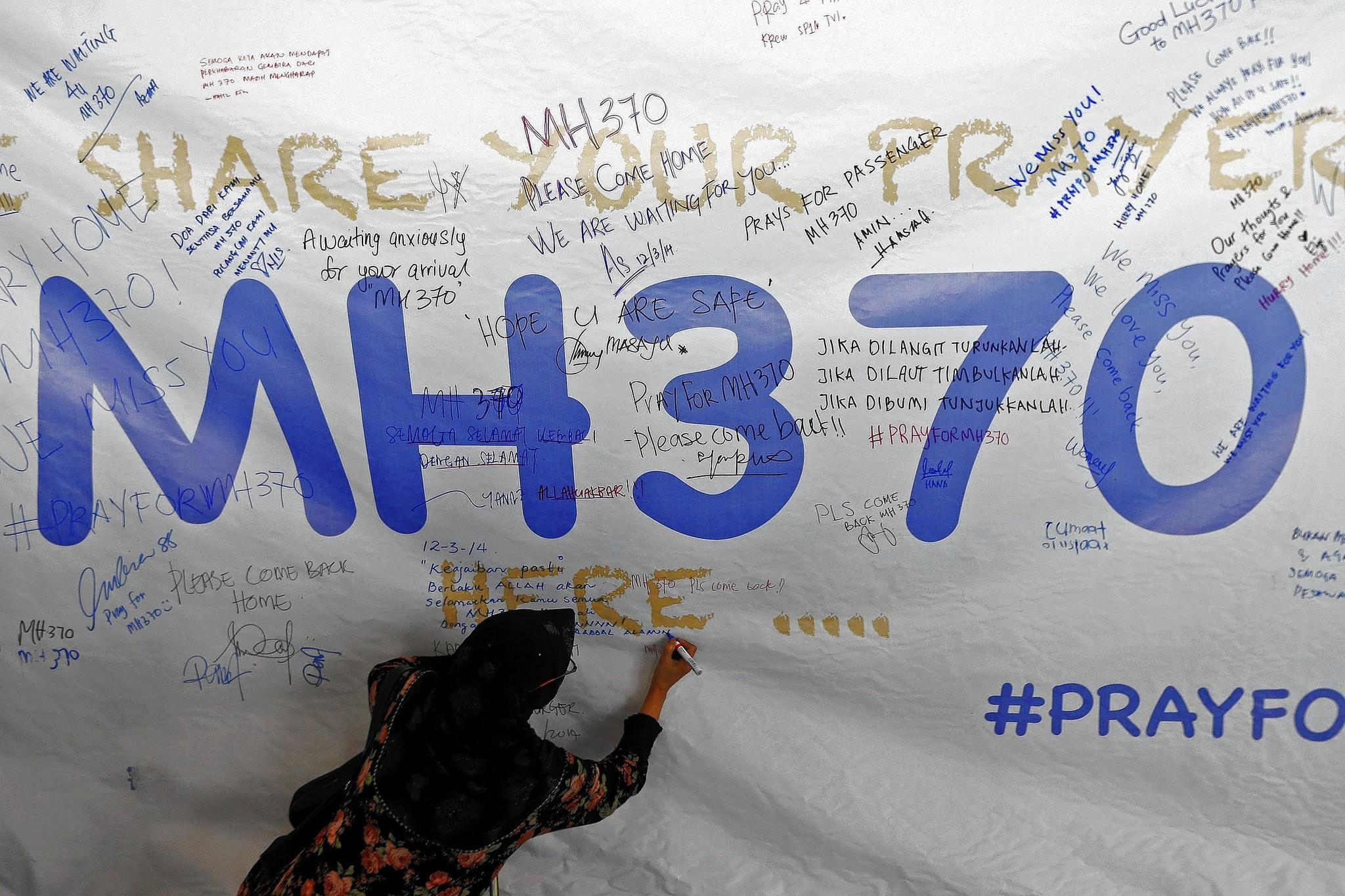 A woman writes a message of support and hope for the passengers of the missing Malaysia Airlines MH370 on a banner at Kuala Lumpur International Airport.