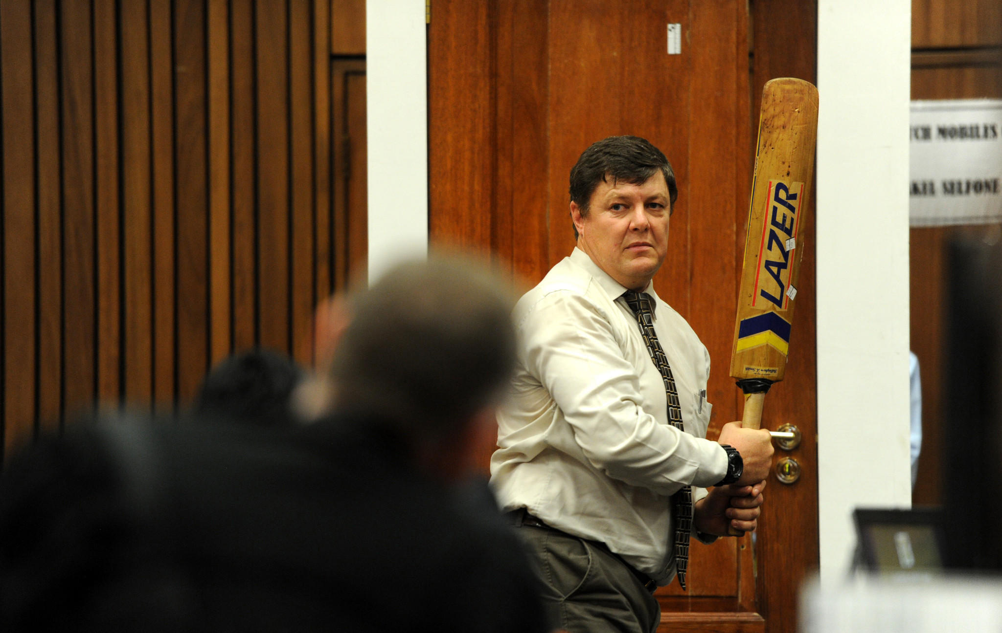 Forensic investigator J.G. Vermeulen, with a cricket bat in hand, on Wednesday demonstrates how the door through which defendant Oscar Pistorius shot and killed his girlfriend could have been broken down with the bat.