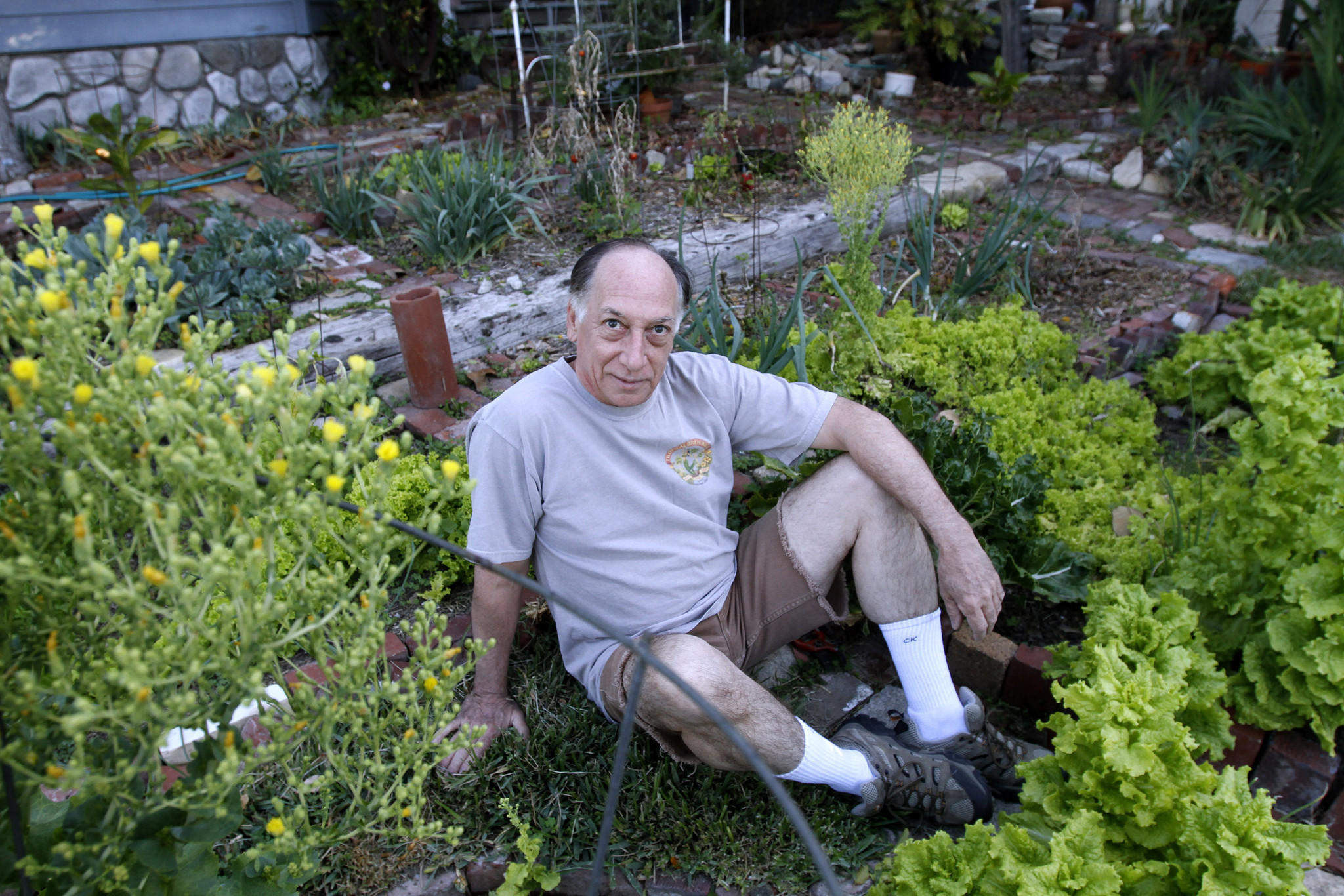 Jim Luna has had a garden in his front yard since he moved into his present home, some 40 years ago, in La Crescenta on Wednesday, March 12, 2014. Luna, who was a ballet dancer and computer tech, lets some of his fruits and vegetables go seed and then spreads that seed around his garden for the next year's crop.