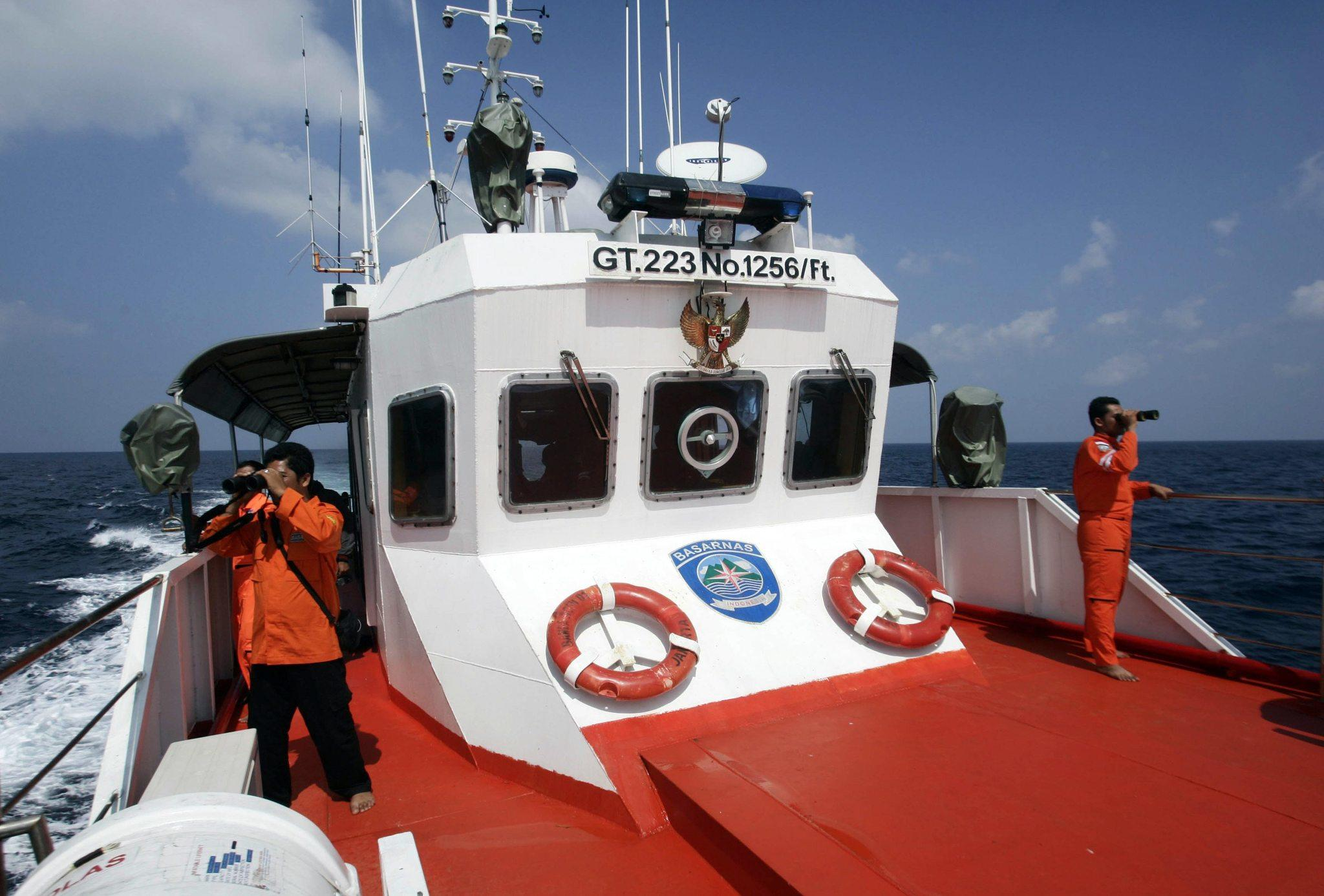 Rescue members on Wednesday use binoculars to look for missing Malaysia Airlines Flight 370 that disappeared from radar screens Saturday in the Straits of Malacca.