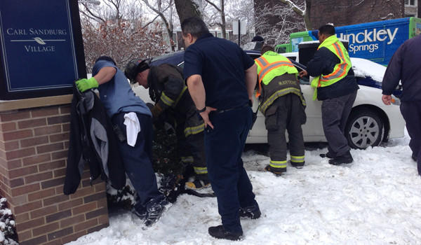 Several Chicago Fire Department personnel speak to a woman seriously injured when she was hit by a taxi on the Near North Side this afternoon as other fire personnel speak to the driver of the taxi.