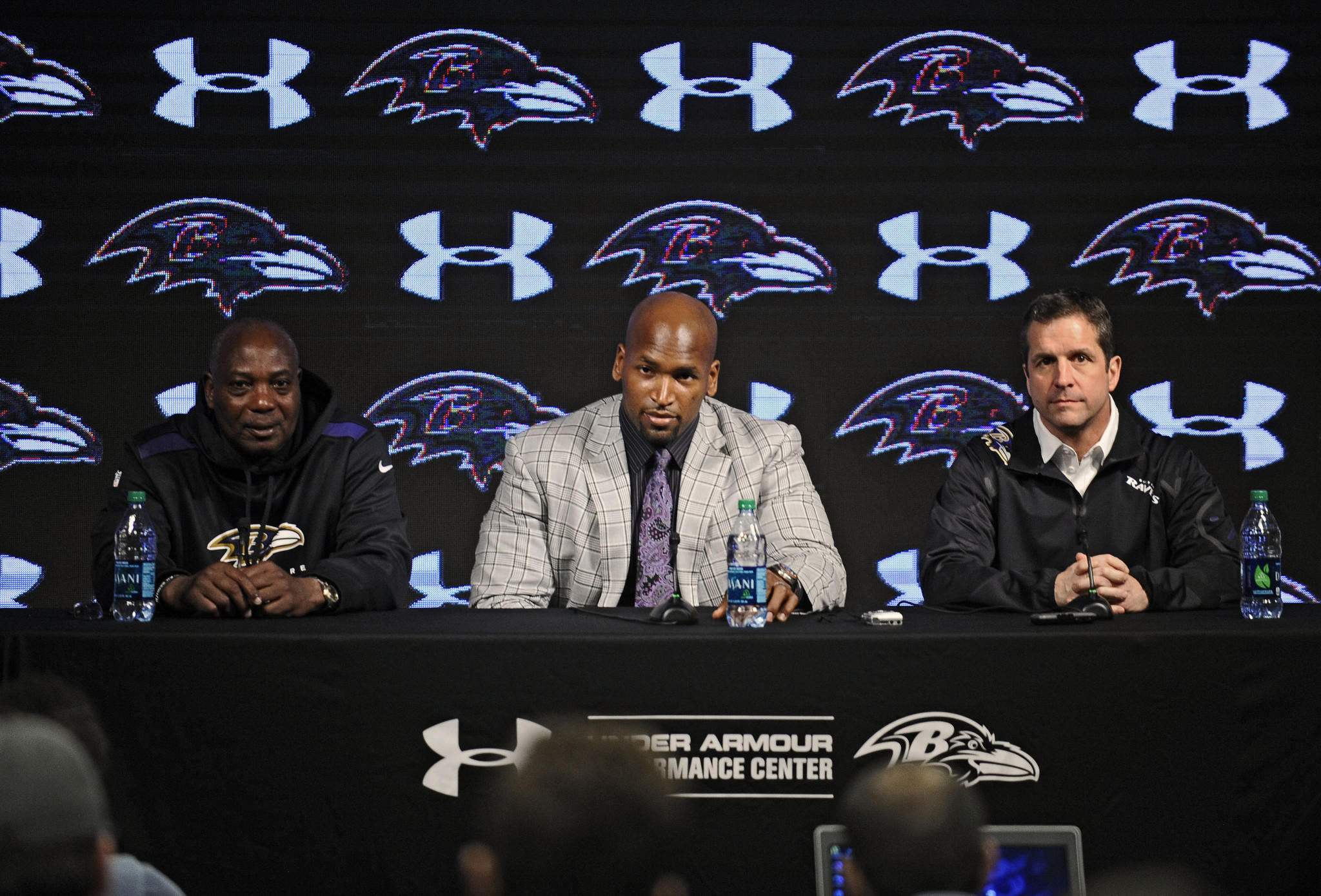 Ravens general manager Ozzie Newsome, coach John Harbaugh sit on either side of offensive tackle Eugene Monroe after he signed his contract extension.