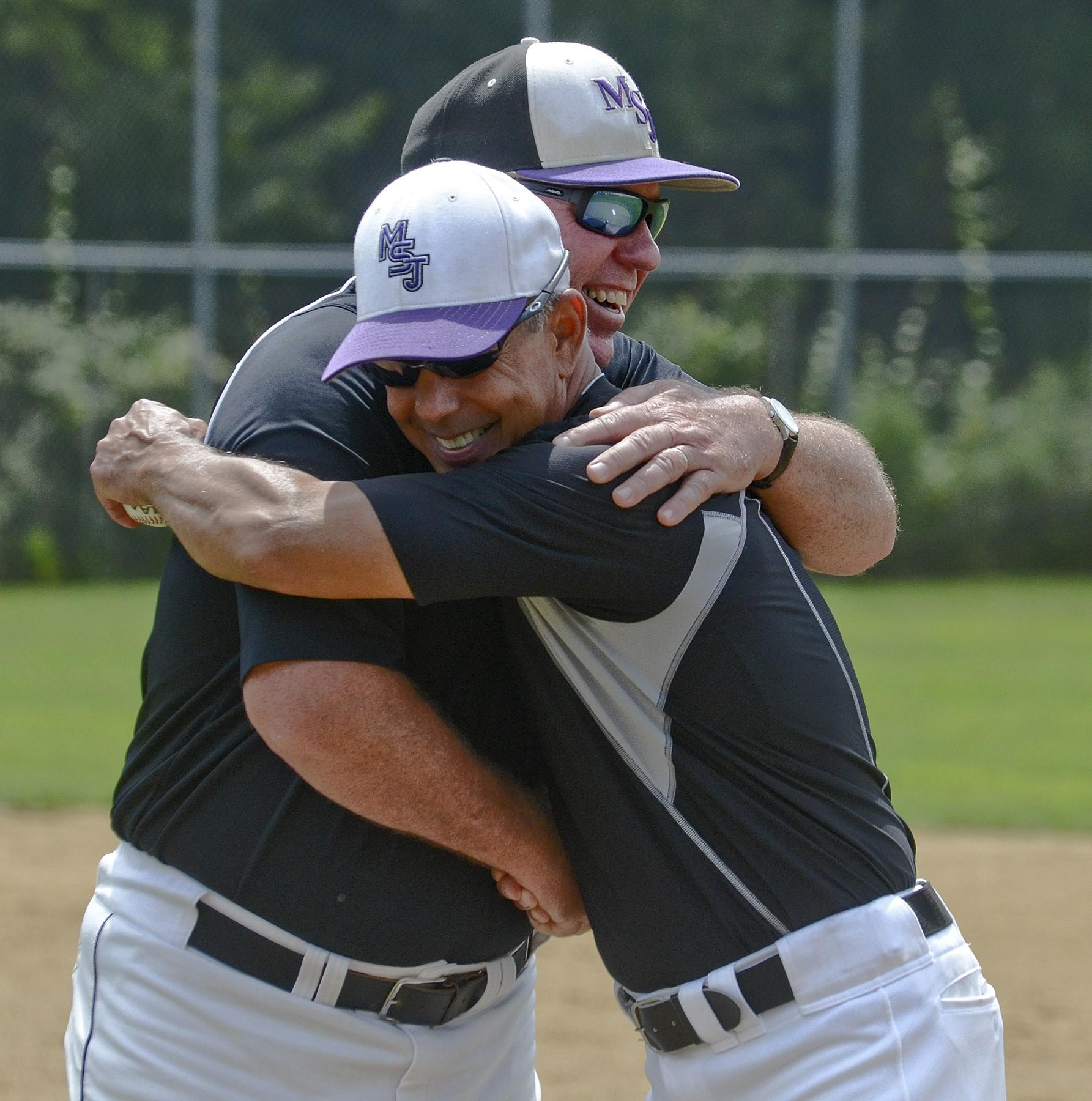 Jody Harris (front), new coach of the Mount St. Joseph baseball team, hugs Dave Norton, outgoing baseball coach at Mount St. Joseph.