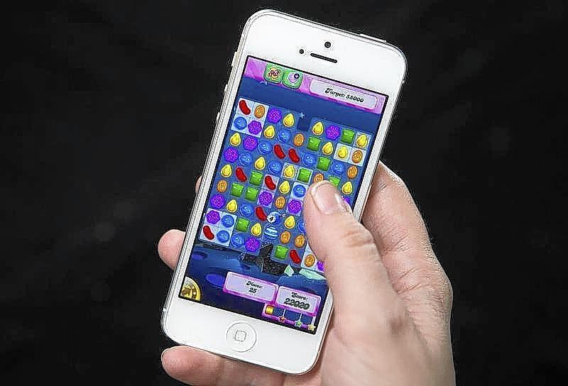 A woman poses for a photo illustration with an iPhone as she plays Candy Crush in New York.