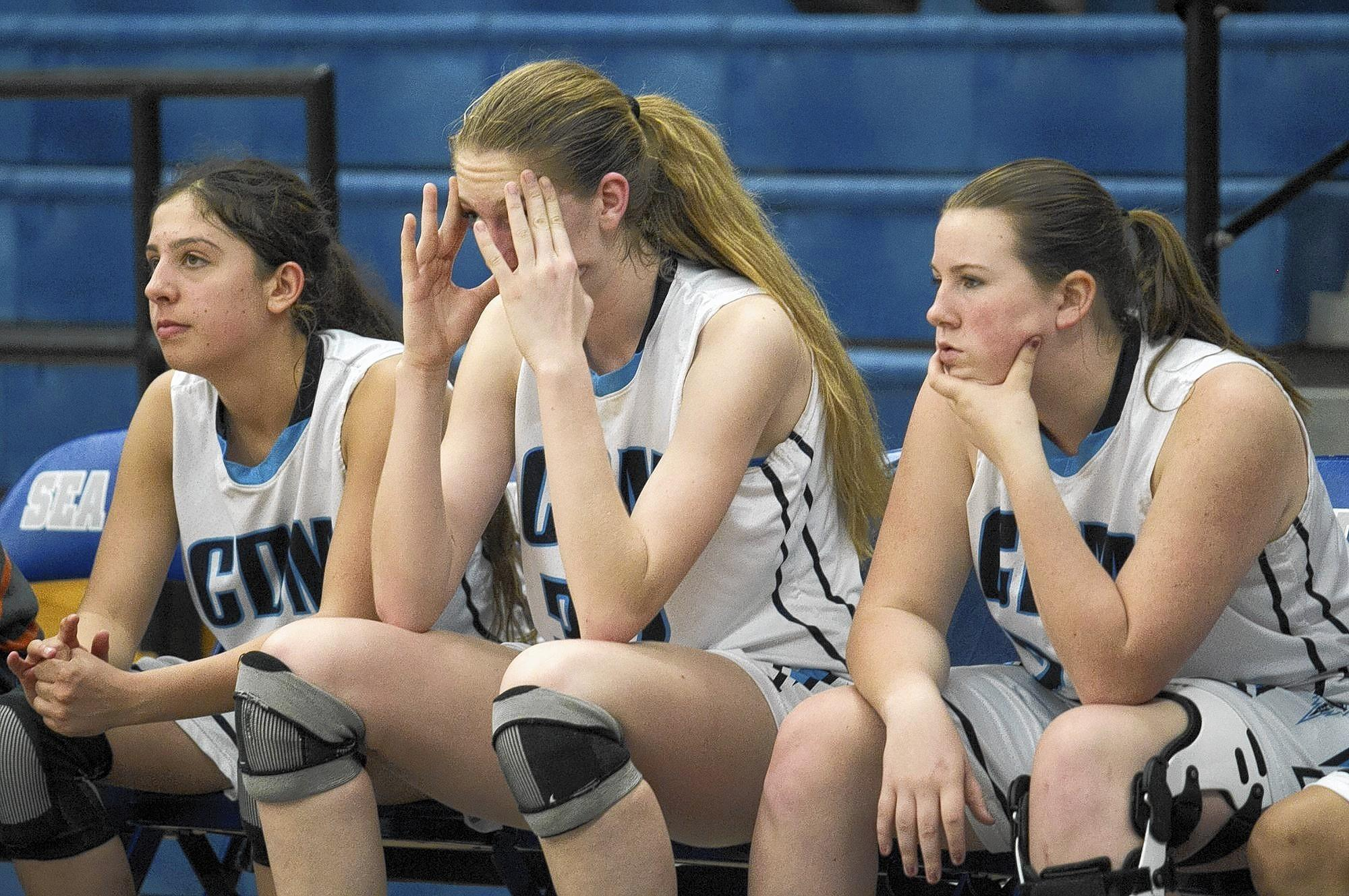 Corona del Mar High's Chanel Wosoughkia, left, Natalia Bruening, center, and Alexa Pridemore watch as the final seconds wind down in a 53-48 loss to Garfield during the CIF State SoCal Regional Division III playoffs on Wednesday.