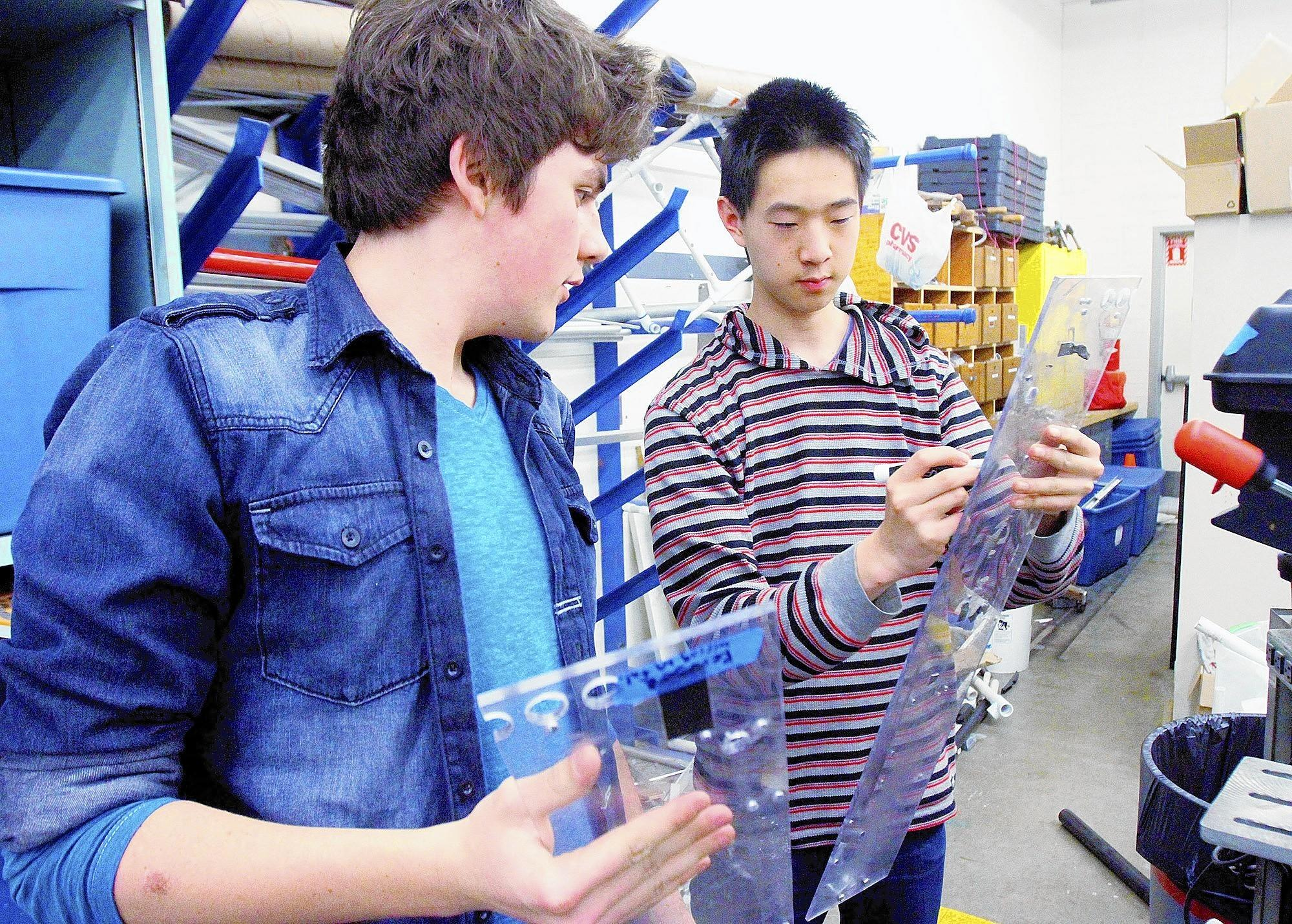 Alex McComb, 16, and club president Philipp Wu, 16, prepare pieces of their backup robot for drilling on the drill press at La Cañada High School on Tuesday, March 11, 2014.