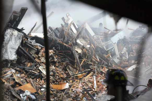 New York City emergency responders search through the rubble at the site of a building explosion in the Harlem section of New York on March 13.