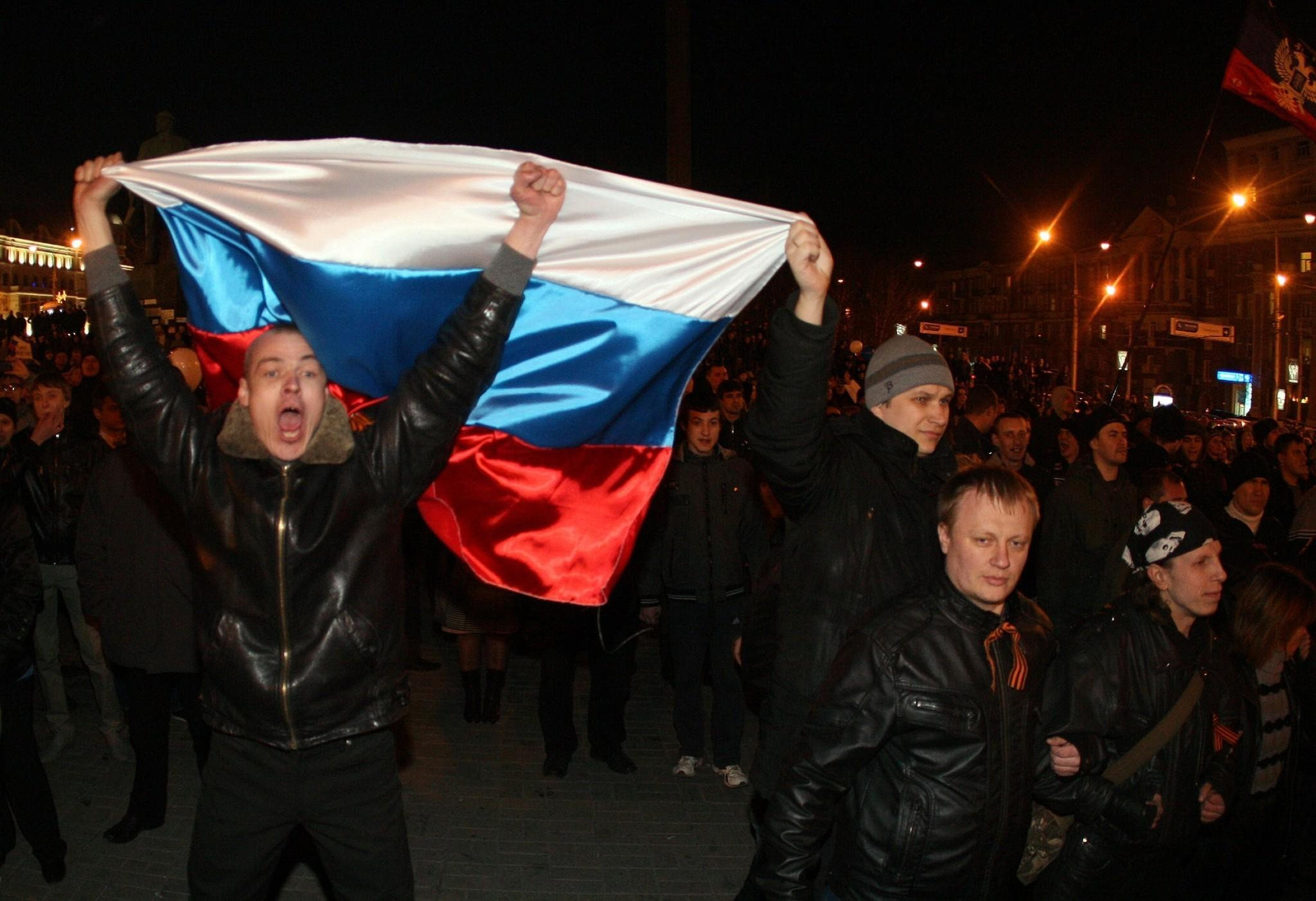 Pro-Russian activists hold Russian flags during a rally in the eastern Ukrainian city of Donetsk on Thursday.