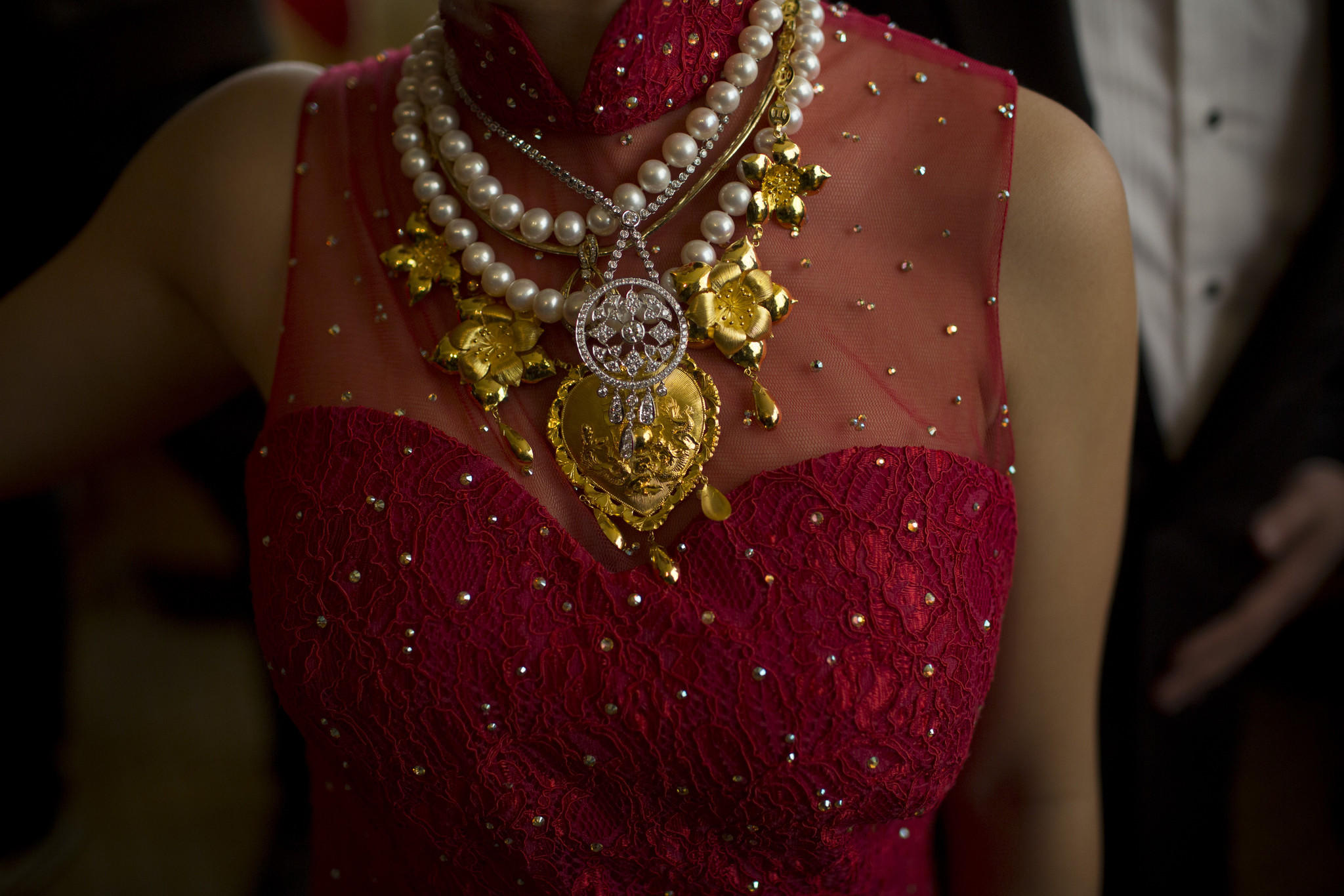 A bride wears gold, pearl and diamond necklaces during the tea ceremony of her wedding in Hong Kong, China, on Saturday, Jan. 25, 2014.