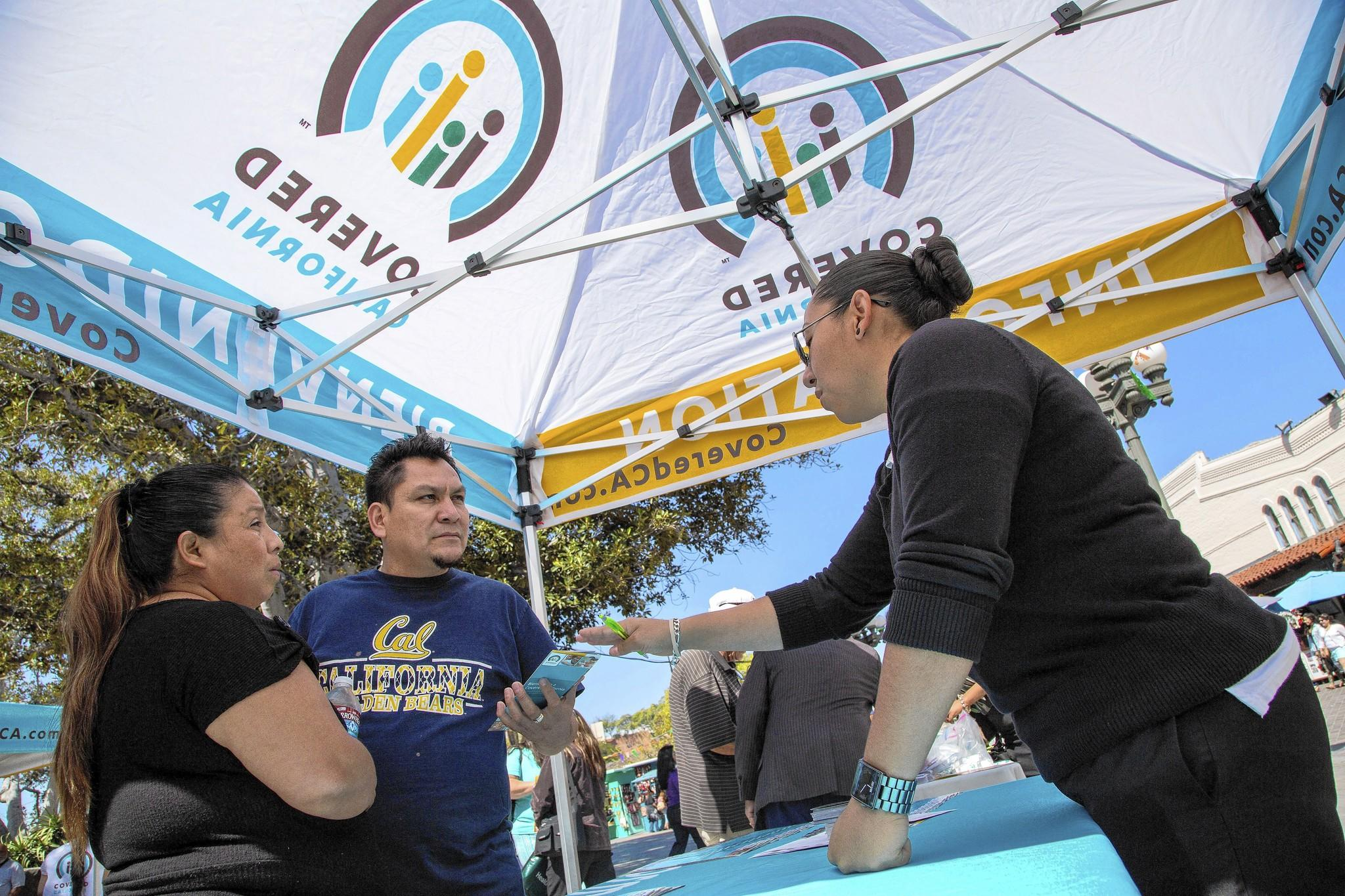 Ana Oliva, left, and Felix Portillo of Los Angeles get insurance information from Valeria Lopez at a Covered California event.