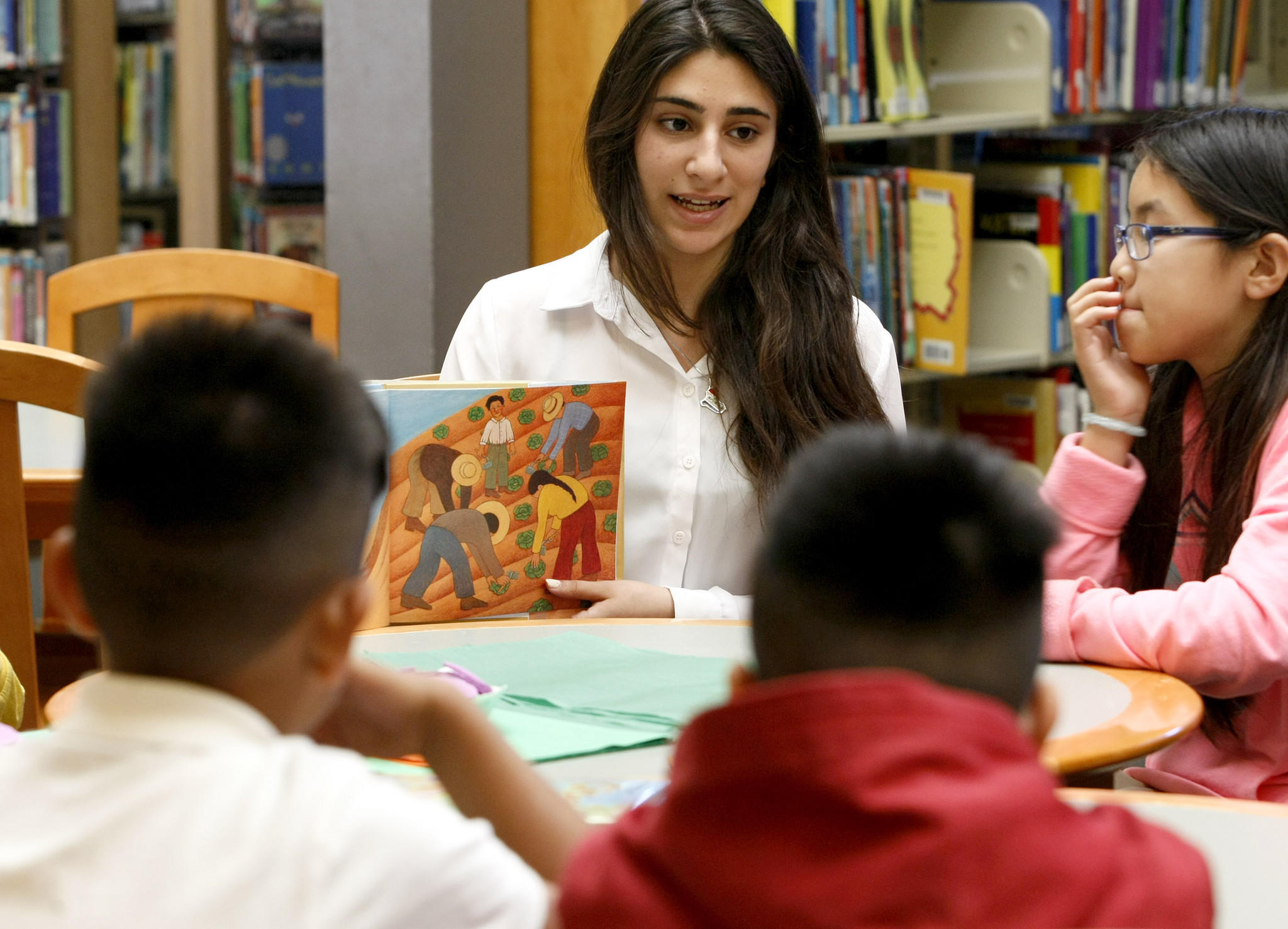 Clark Magnet High School senior Noor Atif read a book about Cesar Chavez to school children at Pacific Park Library in Glendale on Thursday, March 13, 2014. Atif is a voluteer at the library and teaching about Chavez is part of her senior project.