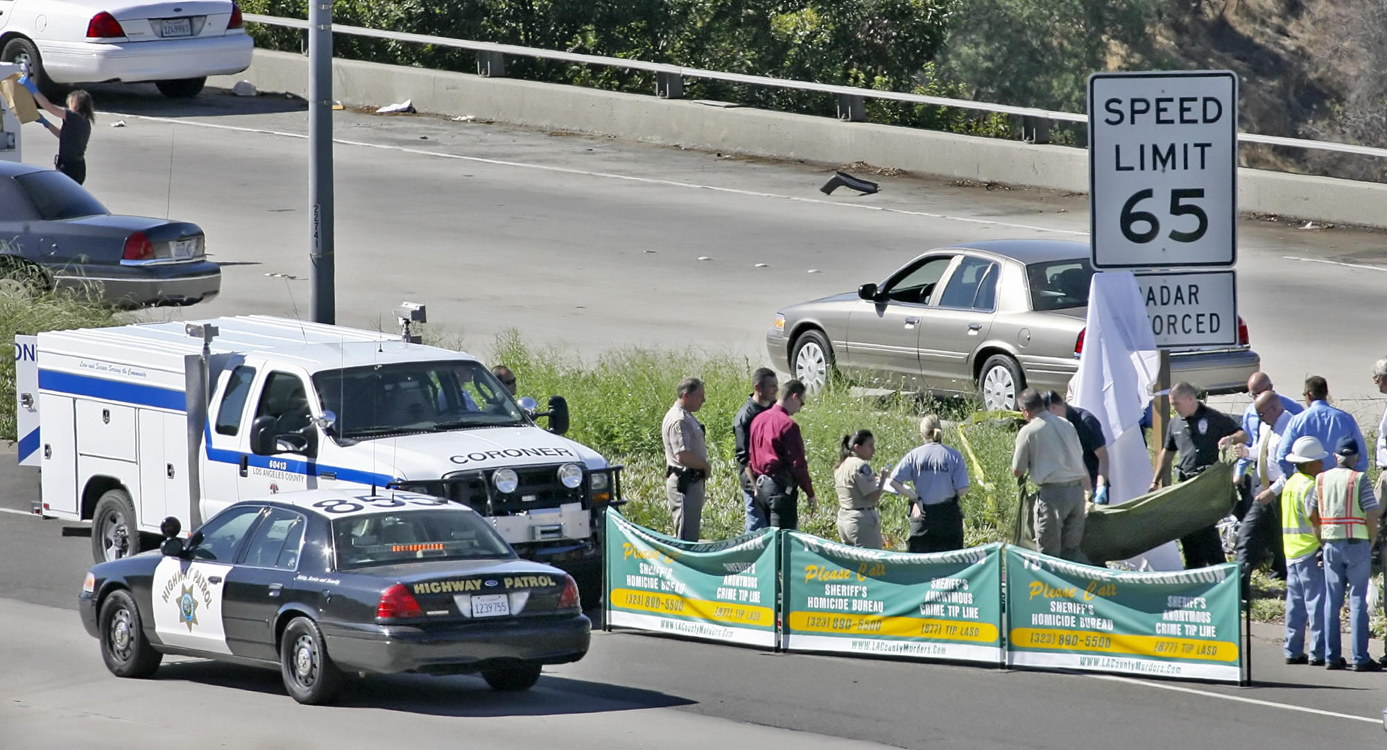 Two men were convicted this week in the 2008 murder of a Mongols Motorcycle Club member gunned down while riding on the Glendale (2) Freeway in 2008. Pictured is the L.A. County Coroner's personnel moving the victim's body on October 8, 2008.
