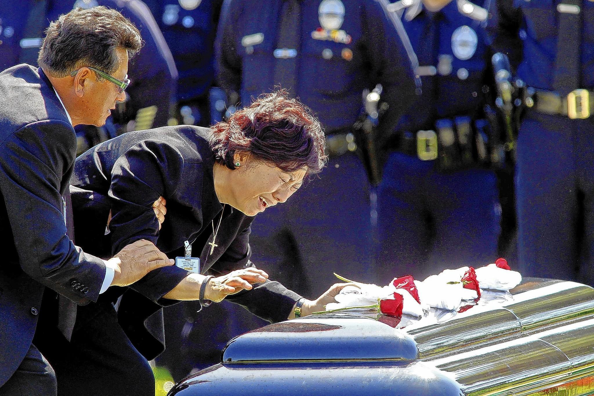 LAPD Officer Nicholas Lee's parents, Heung, left, and Choung, visit his casket during a graveside service at Forest Lawn Memorial Park in Glendale. Lee was killed in a traffic accident last week.