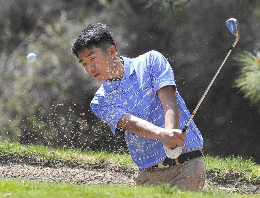 Crescenta Valley High's Paul Park hits out of a bunker outside the first green in a Pacific League golf match at De Bell Golf Club in Burbank on Thursday. (Tim Berger/Staff Photographer)