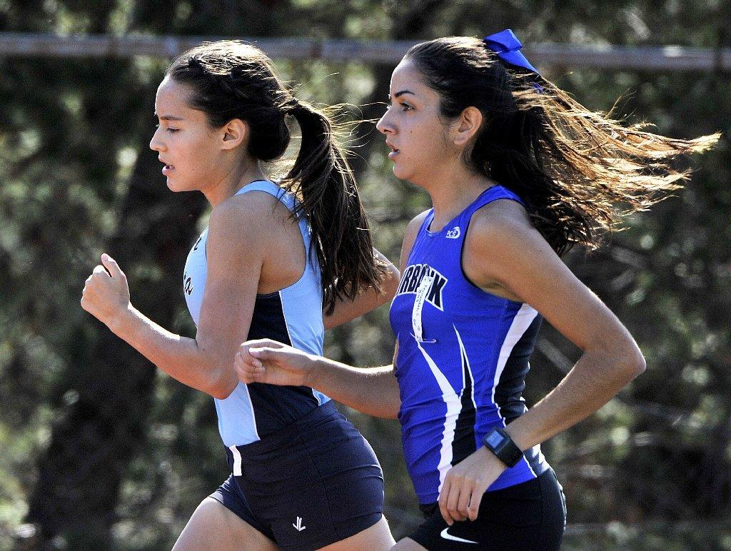 Crescenta Valley High's Megan Melnyk and Burbank's Candela Fernandez battle in the mile in a Pacific League cluster track meet between Crescenta Valley, Burbank and Hoover at Crescenta Valley on Thursday. (Tim Berger/Staff Photographer)