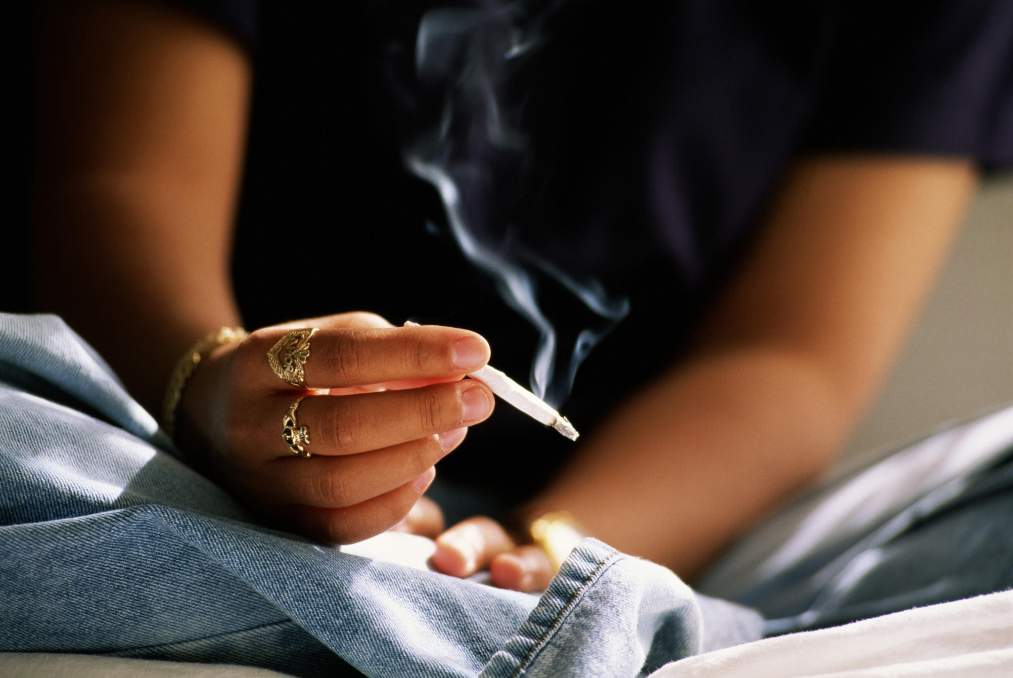 A teenager smokes a hand-rolled cigarette.
