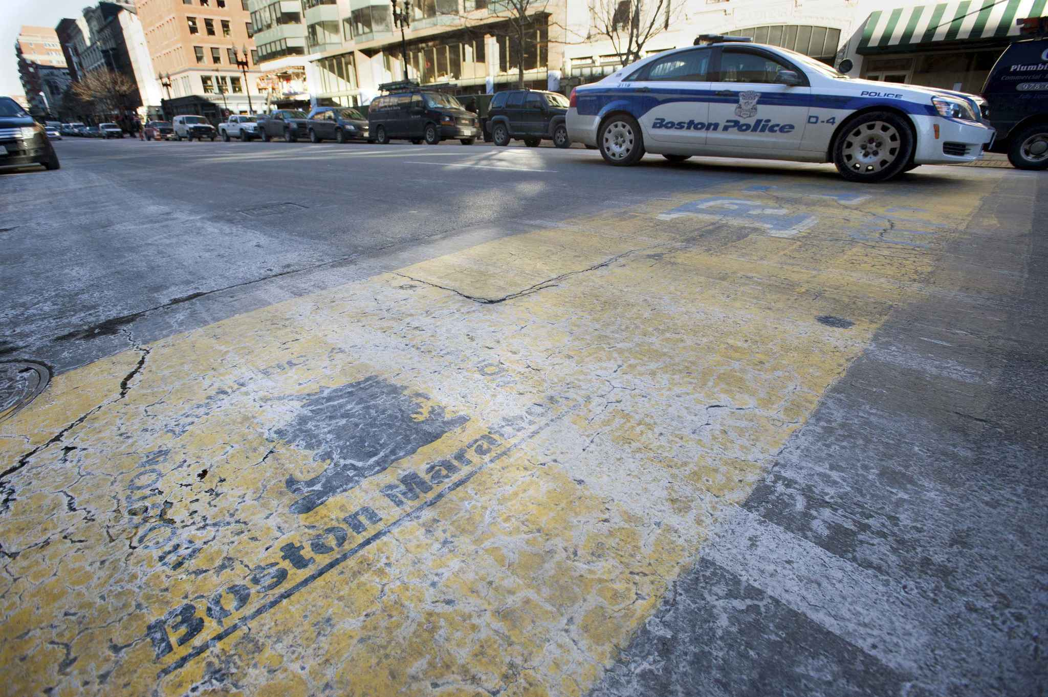 A Boston police car drives over the painted finish line from last year's Boston Marathon. Even as police prepare for a massive presence at Boston's first marathon since the 2013 bombing attack that killed three people and injured 264, officials acknowledge the sheer scale of the event poses inevitable security risks.