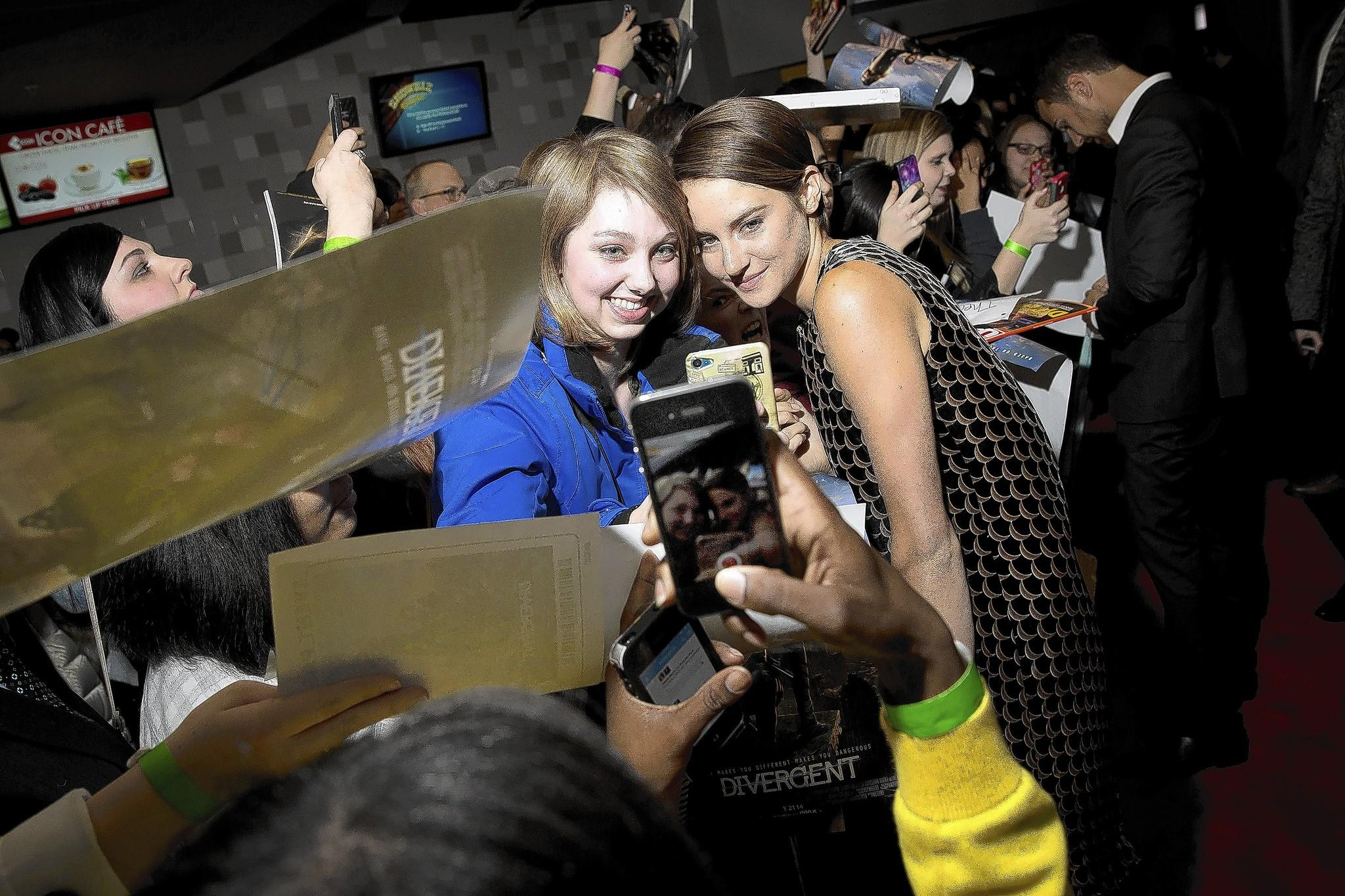 """Shailene Woodley, right, of the film """"Divergent"""" poses with fan Ali Walder, left, of Milwaukee, Wis., on the red carpet at the Showplace Icon Theater in Chicago."""