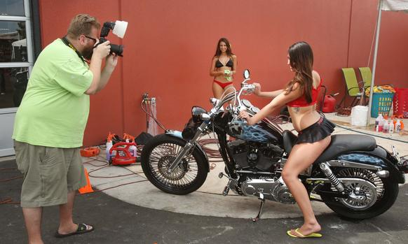 "Photographer Robert Bryant photographs girls from Baywash bikini car wash who were washing bikes for visitors to Orlando Harley-Davidson on Tuesday. With Bike Week underway in Datona Beach, motorcycle sellers in Orlando are in full swing. Orlando Harley Davidson promises revelers that they ""have their bike week p"