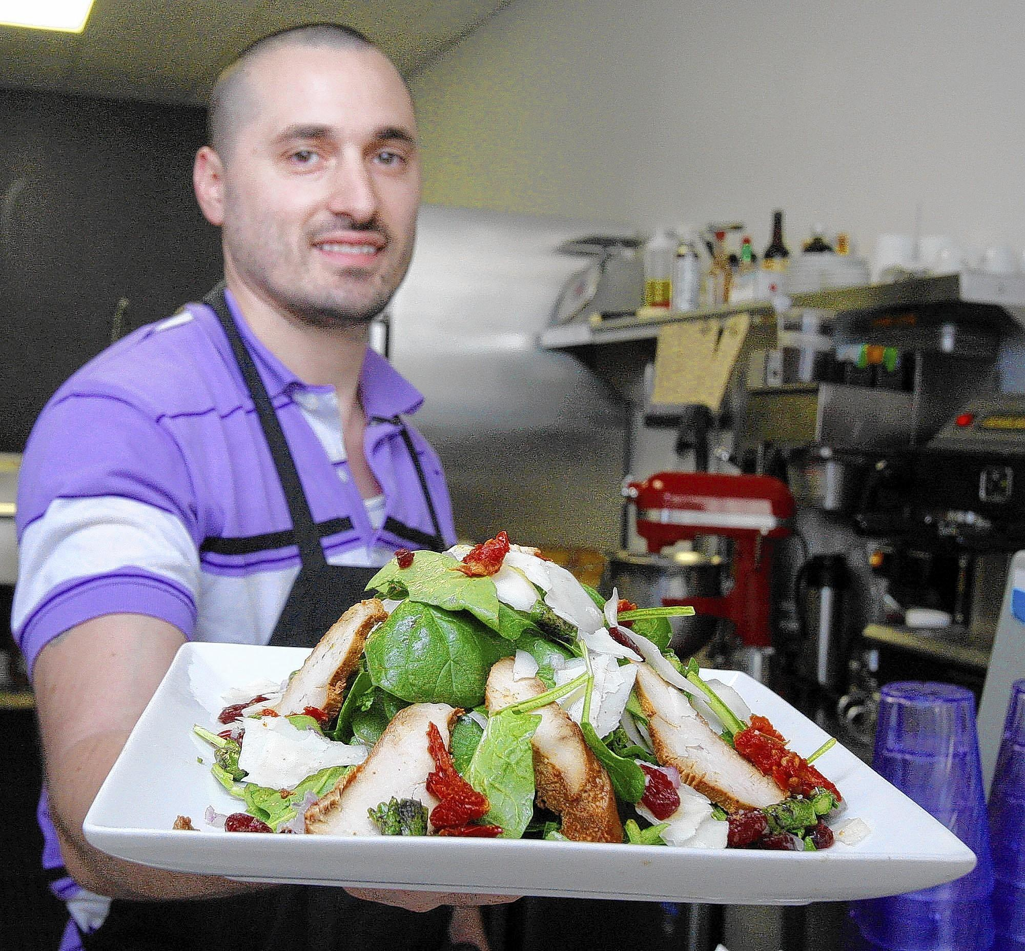 Chef Aurelien (Tony) Mosconi holds a La Chicken Manchego Salad with spinach, grilled chicken, imported Manchego cheese, red onions, cranberries, sundried tomatoes, asparagus, homemade raspberry vinaigrette at Monsieur Crêpe in Sierra Madre on Friday, March 7, 2014.