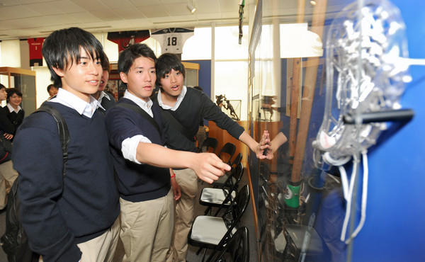 """Keio Senior High School lacrosse players (from left) Jun Hashizume, Tomohito Kurita and Tomoki Hashida look at artifacts at the U.S. Lacrosse Museum. The students left for their two-week tour of the U.S. just days after the earthquake and <a class=""""taxInlineTagLink"""" id=""""EVWAN00003"""" title=""""Japan Earthquake and Tsunami (2011)"""" href=""""/topic/disasters-accidents/earthquakes/japan-earthquake-tsunami-%282011%29-EVWAN00003.topic"""">tsunami</a> devastated Japan."""