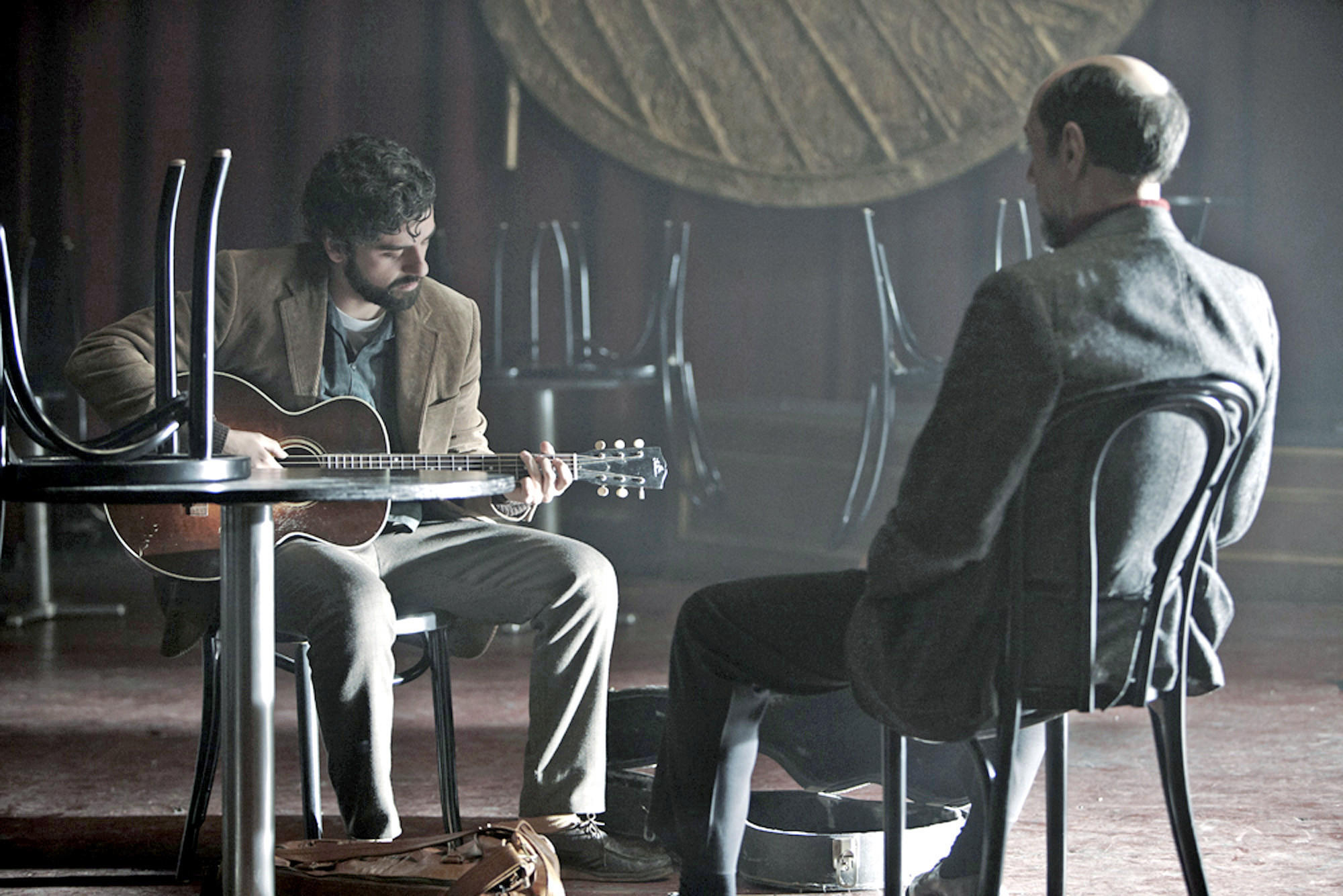 "Folk singer Llewyn Davis (Oscar Isaac) auditions for a Chicago club owner (F. Murray Abraham) in the Coen Brothers' ""Inside Llewyn Davis."""
