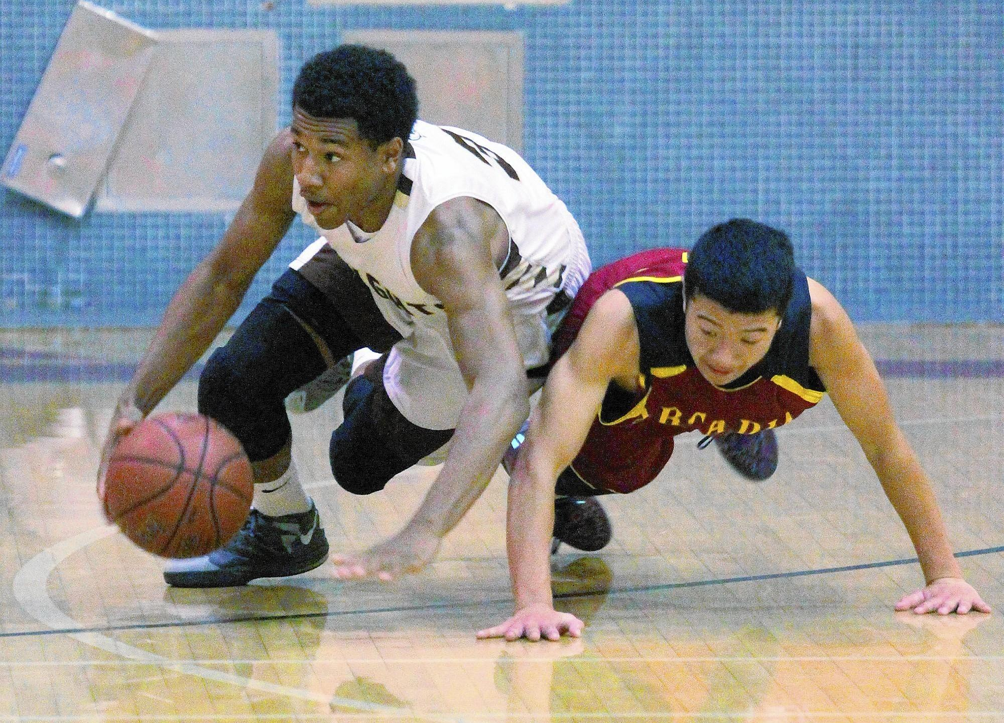 St. Francis' Kyle Leufroy dives for and gets a loose ball against Arcadia's Brendan Tran in the La Cañada Holiday Classic boys basketball tournament at La Cañada High School on Tuesday, December 17, 2013.