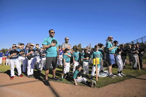 Teams listen to the national anthem during the opening day ceremony for the Newport Beach Little League on Saturday.
