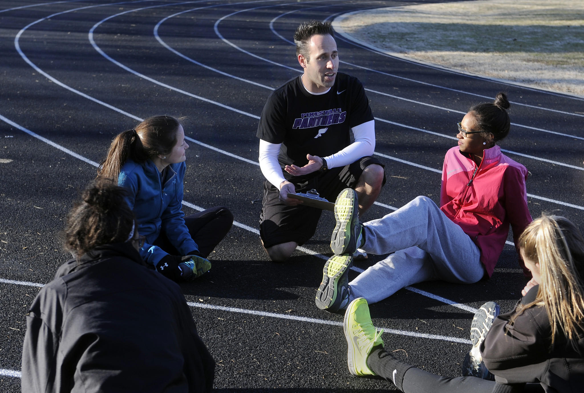 Pikesville girls track coach Adam Hittner talks with some of the runners as they stretch on the track.