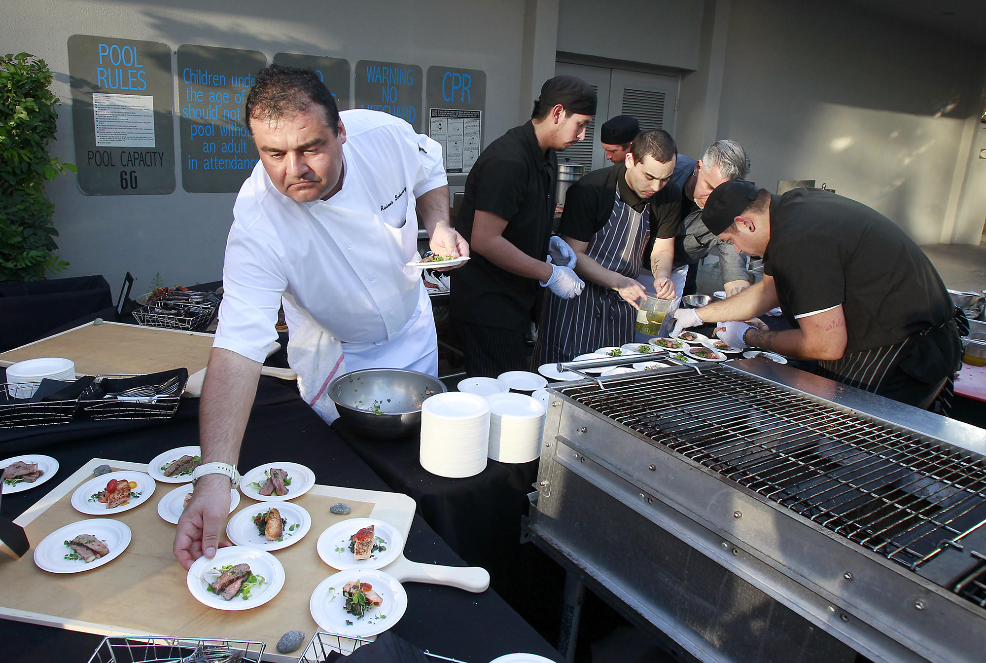 Chef Rainer Schwarz, left, and his crew work diligently to serve grilled tavern rib-eye steaks and bay salmon for guests during grand opening of Fireside in the Crowne Plaza hotel in Costa Mesa on Thursday.