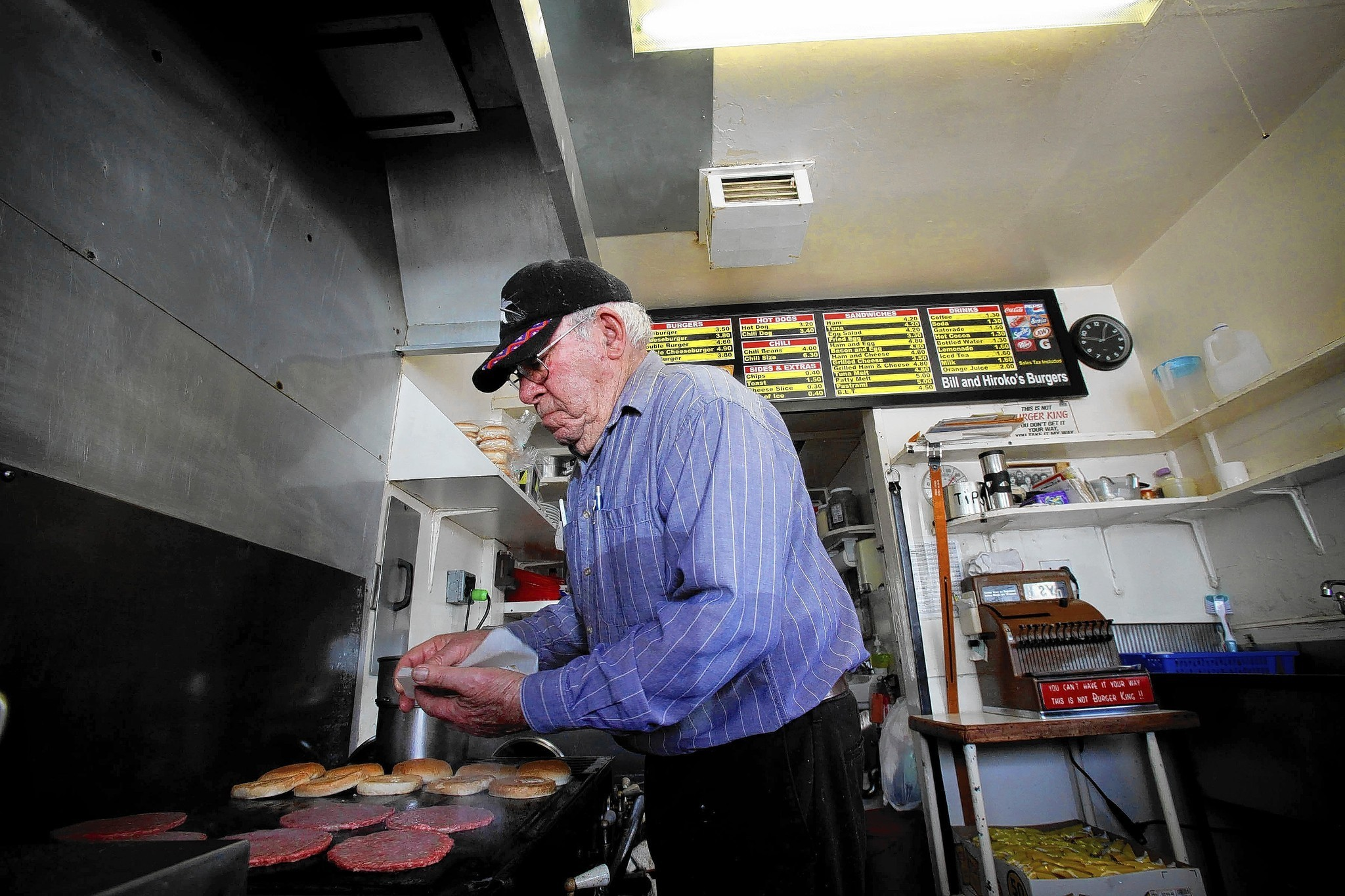 Bill Elwell, 87, plops patties onto the old flattop grill at his hamburger stand, Bill & Hiroko's Burgers, on Oxnard Street where Van Nuys meets Sherman Oaks. He crankily says he doesn't want any more customers, but they just keep showing up anyway.