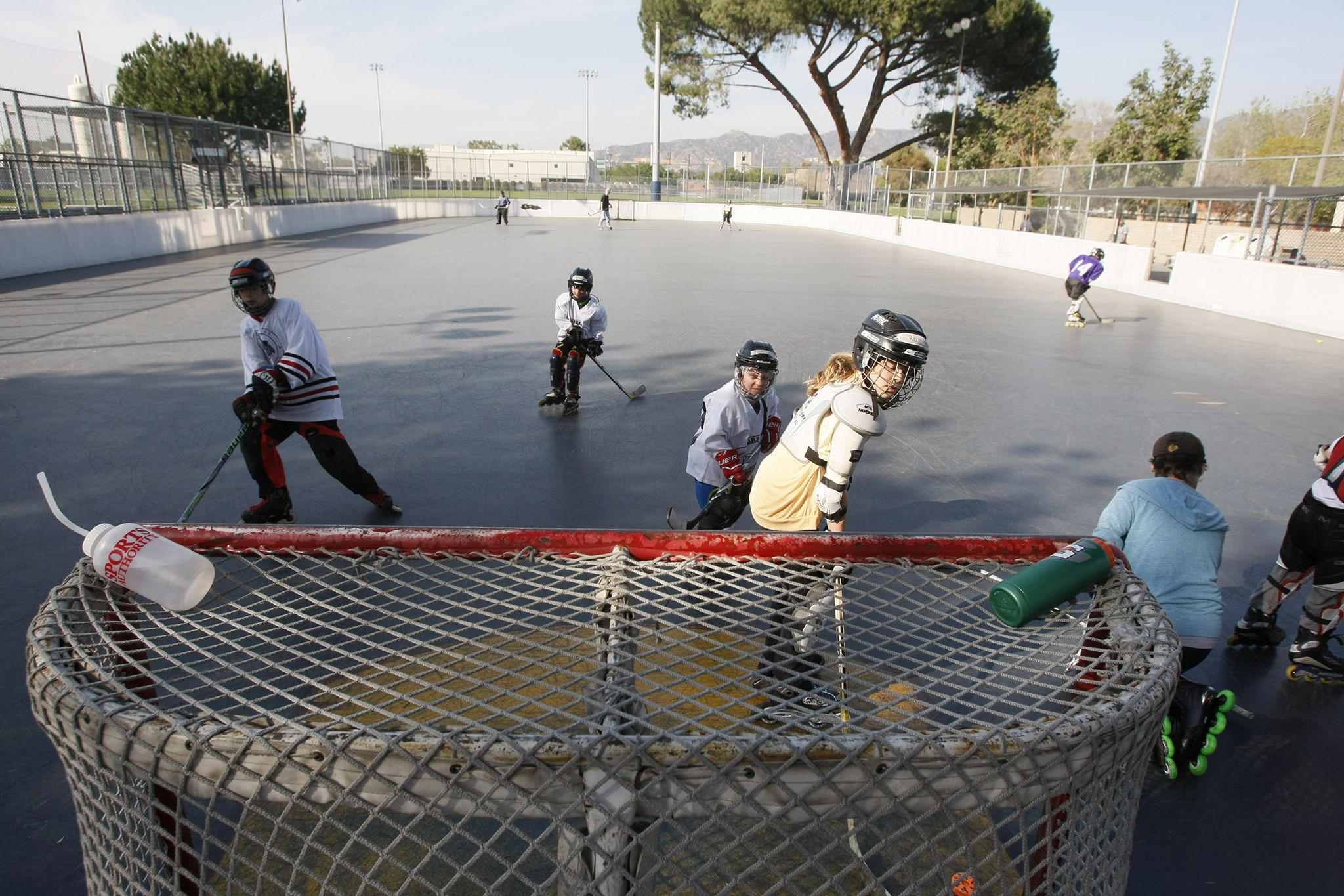 Children play at the Ralph Foy Park roller hockey rink in Burbank on Friday, March 14, 2014.