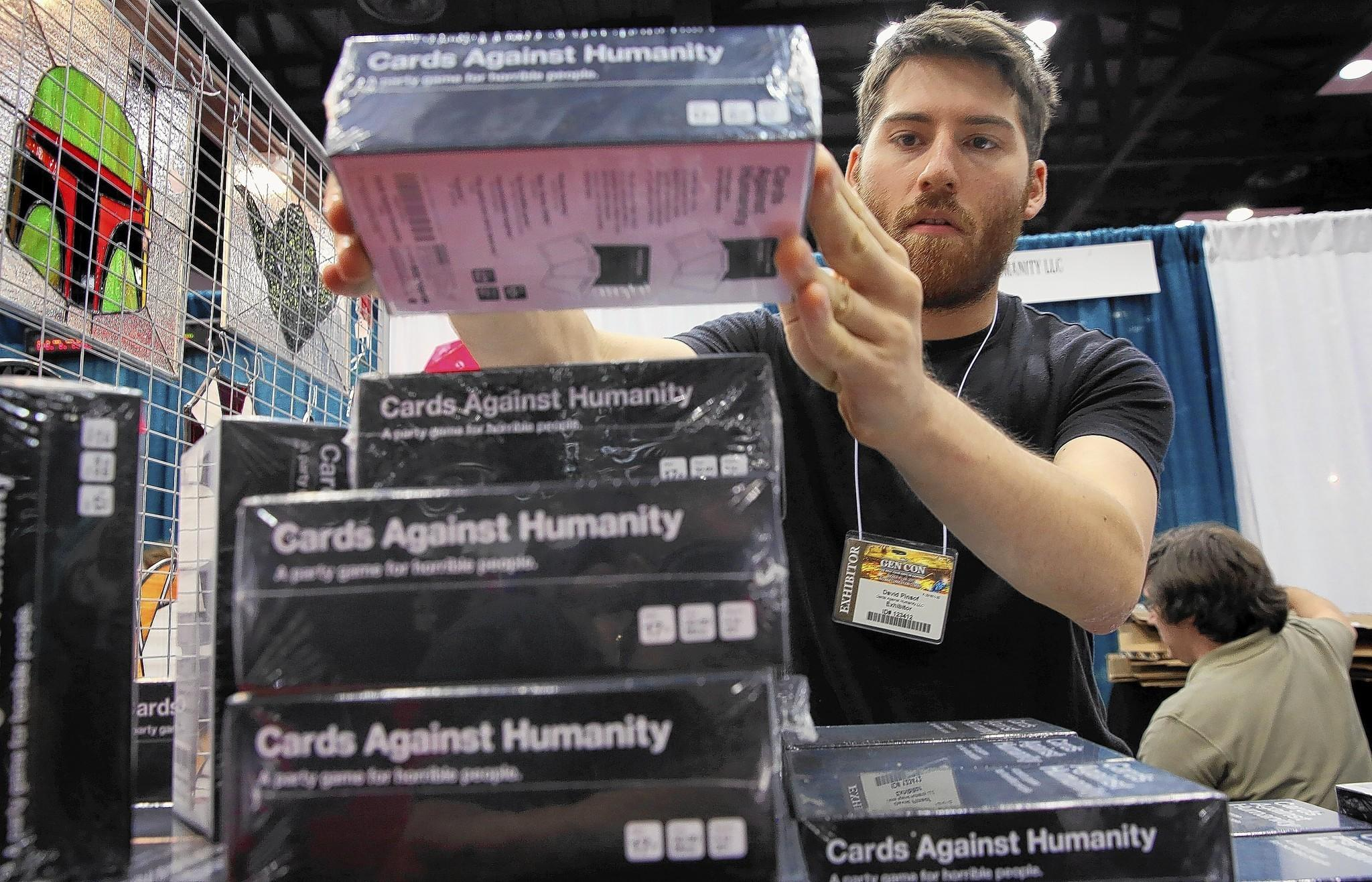 At a gaming conference last year, Dave Pinsof stacks boxes of Cards Against Humanity, which has topped card and game sales on Amazon for several years. Pinsof is one of the creators of the game.