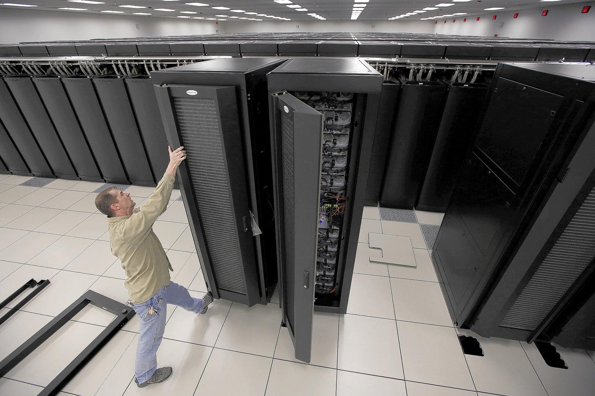 At the University of Illinois at Urbana-Champaign, data archive administrator Jim Glasgow installs water cooling doors this month on two racks at the Blue Waters supercomputer, one of the world's most powerful.