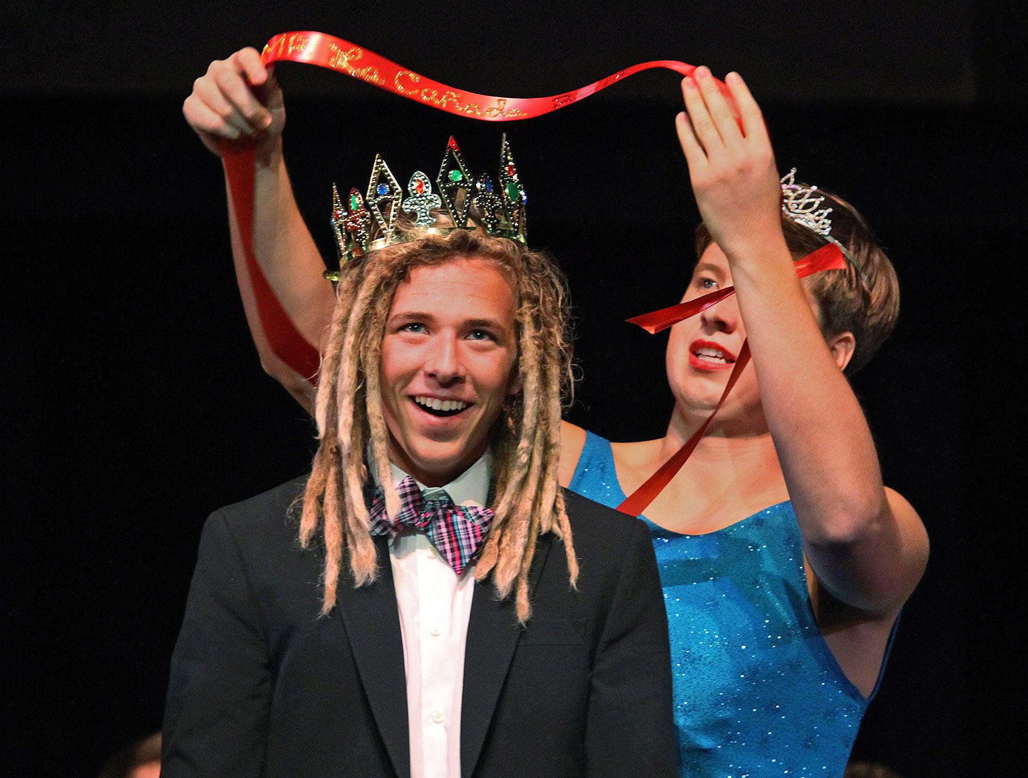 Griffin Van Amringe is crowned and sashed the winner of the contest by Reed Buck who is wearing a tiara and a dress in the first ever Mr. La Canada beauty pageant hosted by the La Canada High School' ASB on Friday, March 14, 2014. The pageant, which was at La Canada High School, was a fundraiser for the St. Baldrick's Foundation to Conquer Childhood Cancers.