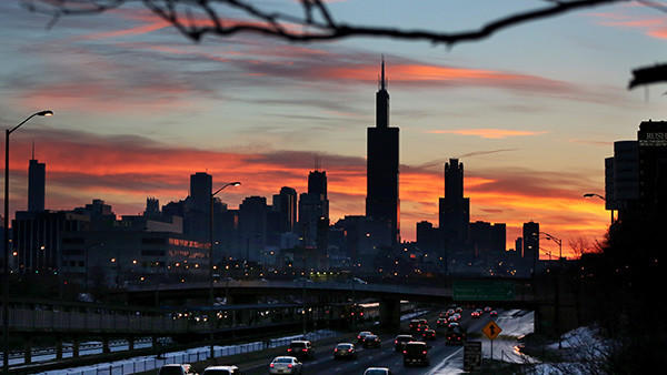 Morning commuters move eastbound on the Eisenhower Expressway as the rising sun silhouettes the city skyline Friday.