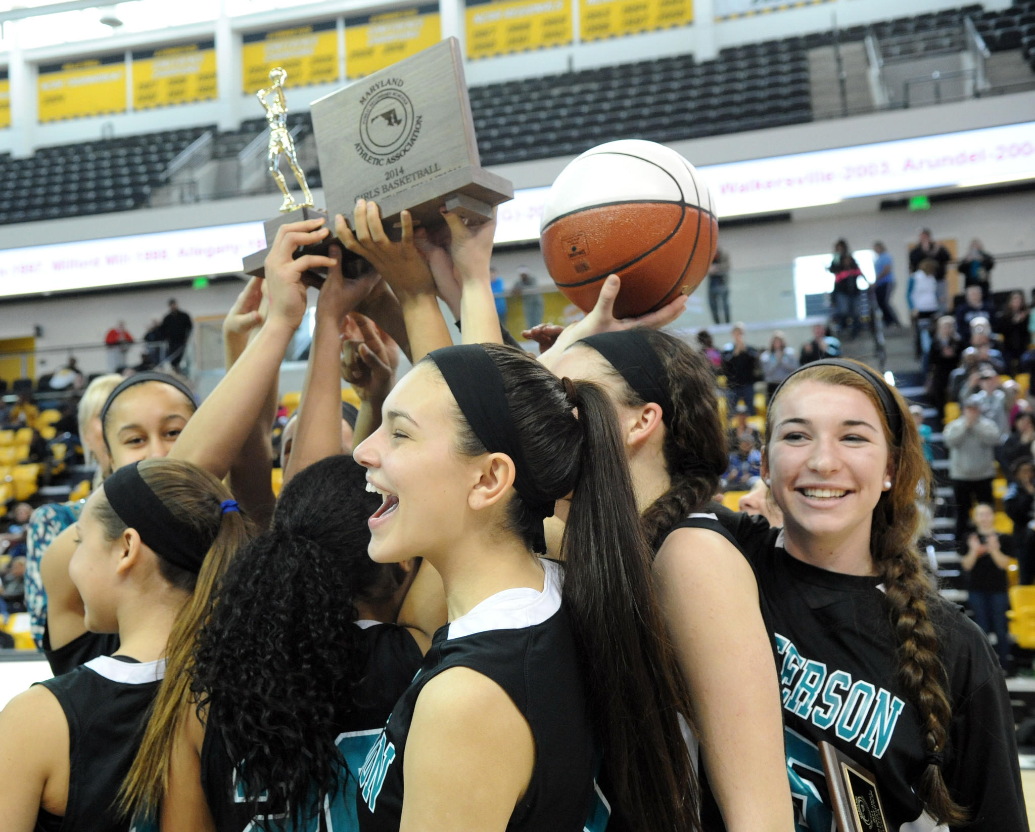 The Patterson Mill Lady Huskies basketball team celebrates aftert their win over Calvert in Saturday's Class 2A State Championship game at the SECU Arena.