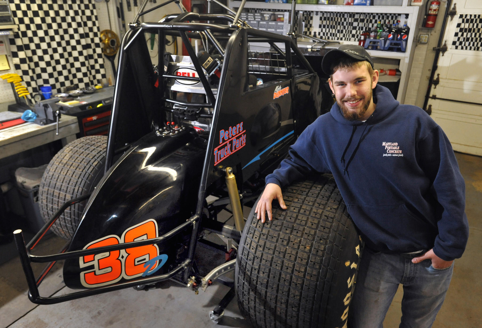 Kyle Denmyer, 16, in his family's garage with the 358 Sprint Car (700 horsepower) that he and his team are almost finished rebuilding. He's racing at Lincoln Speedway in Abbottstown, Pa.