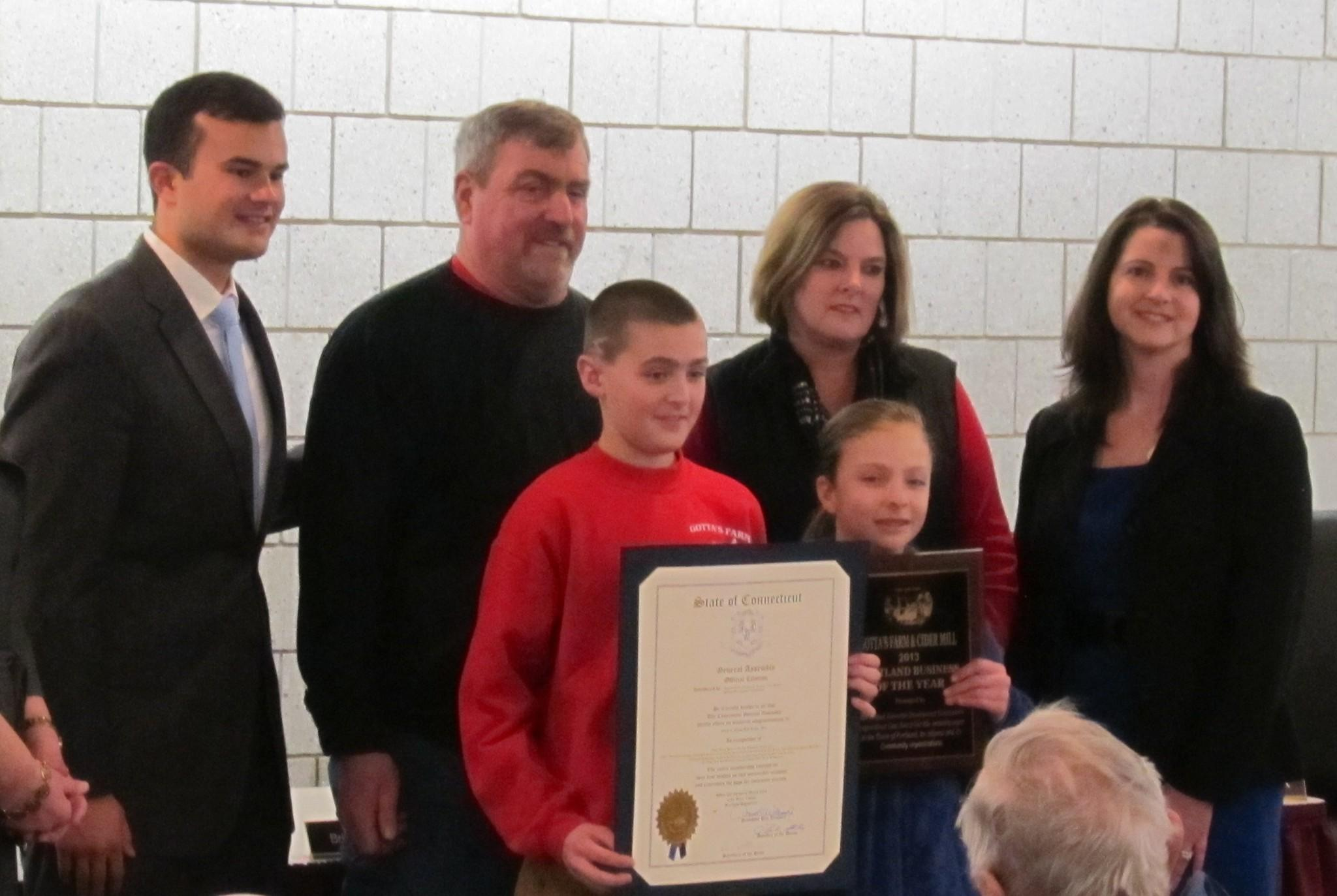 State Senator Art Linares, Richard Gotta, Jackie Gotta, and State Representative Christie Carpino pose with the next generation RJ and Elizabeth Gotta, holding the Economic Development Commission Award and a citation of the Connecticut Legislature.