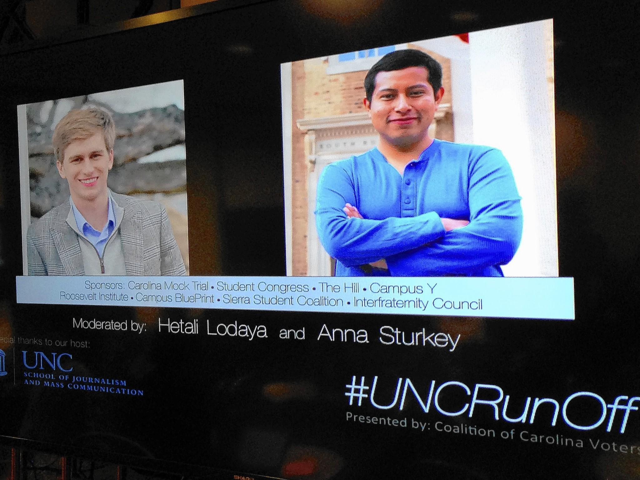 A display screen during an election debate at the University of North Carolina shows the runoff candidates for student body president, Andrew Powell, left, and Emilio Vicente.