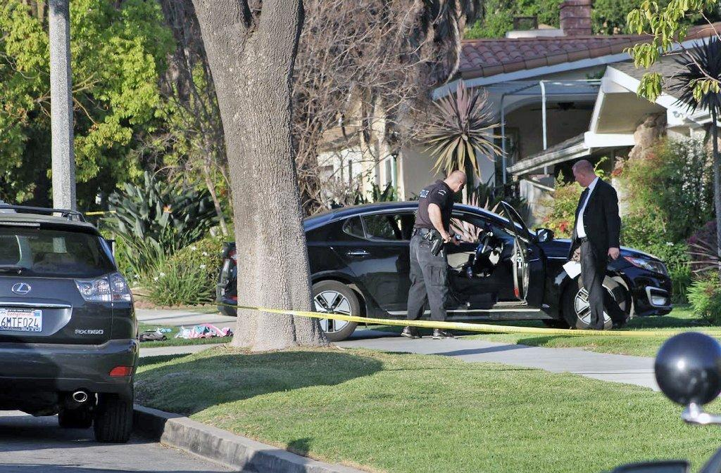 A Burbank police officer and detective look at a car driven by a man stabbed on Saturday. Police said a second man in the car had also been stabbed.