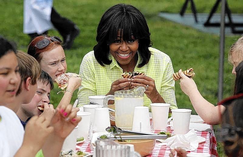First lady Michelle Obama eats after harvesting vegetables from the summer crop from the White House Kitchen Garden in Washington.