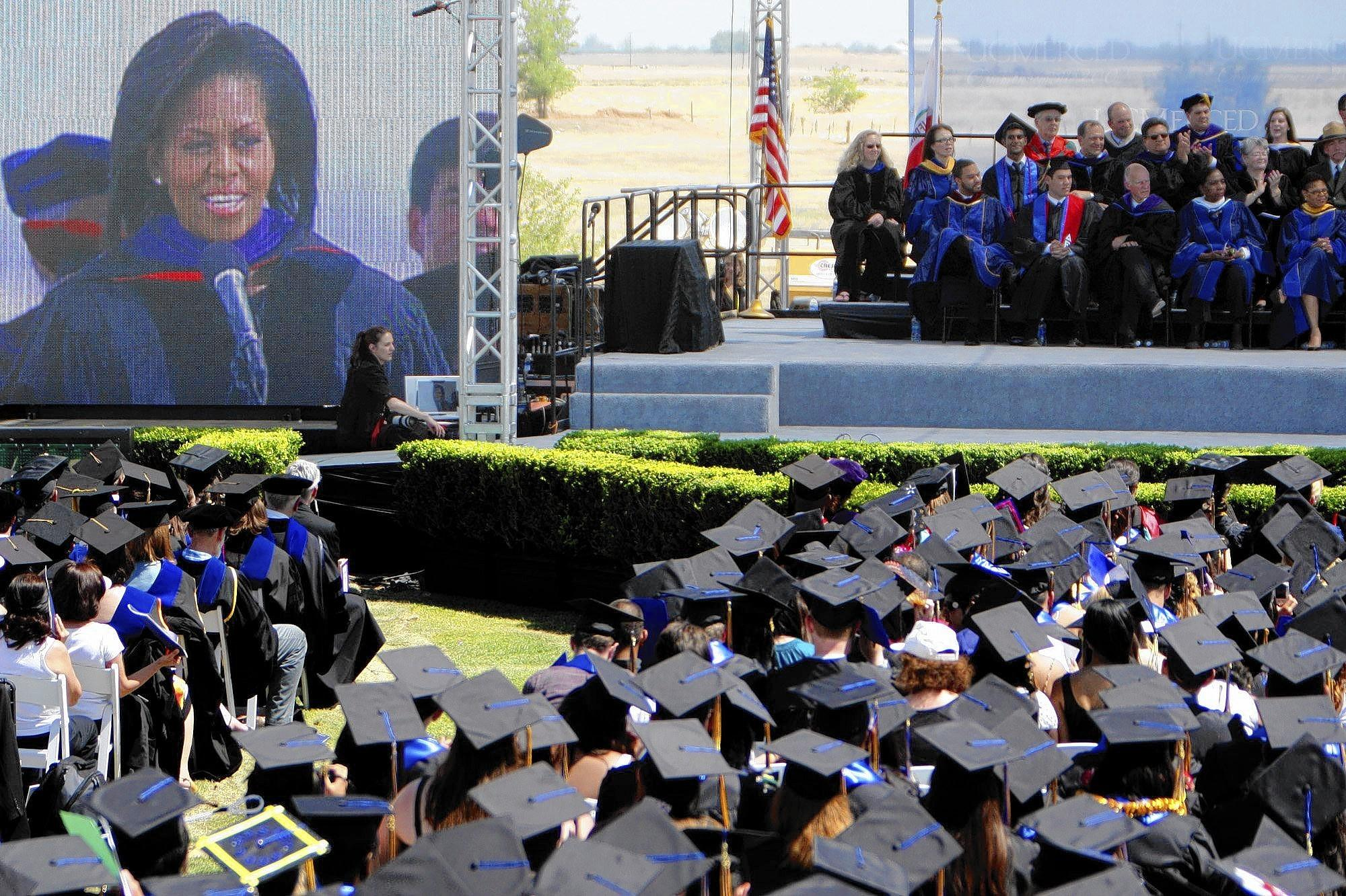 "First Lady Michelle Obama, projected on an LED screen, gives the commencement address for the first full graduating class at UC Merced in May 2009. Students and staff had bombarded her with postcards, valentines and a video in which the narrator says: ""Dear Michelle, we believe in you and we would be honored if you could be our keynote speaker."""