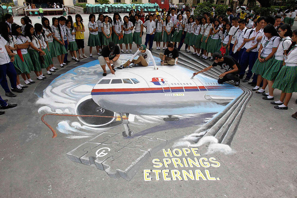 Students watch as a group of artists put the finishing touches to a 3D artwork, based on the missing Malaysia Airlines flight MH370, that was painted on a school ground in Makati city in Manila on March 17.
