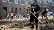 Musicians, volunteers dig up school parking lot to help bay