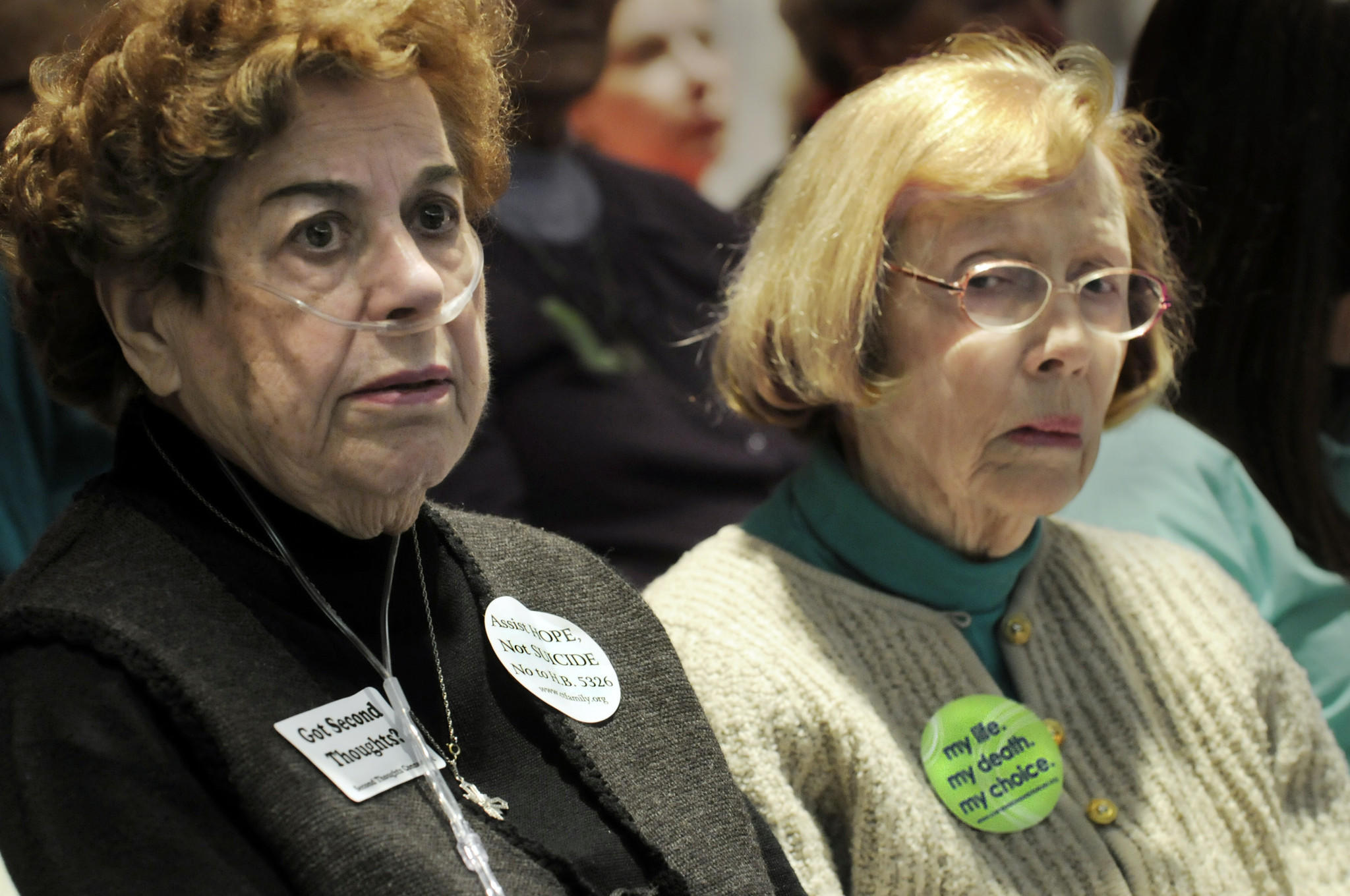 Patricia Conran, left, of Hartford, wore her stickers stating her opposition to the bill while Sally Hart of Essex, right, wore her stickers in support of the right-to-die bill.