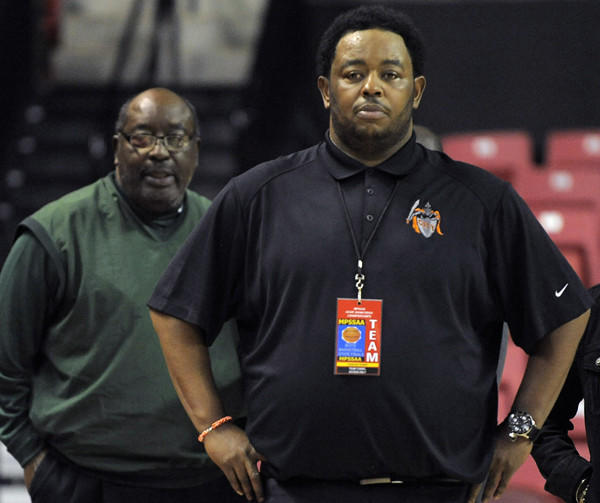 Baltimore City coordinator of athletics Bob Wade, left, stands behind his son, City boys basketball coach Daryl Wade during the Class 3A championship game Saturday at Comcast Center.