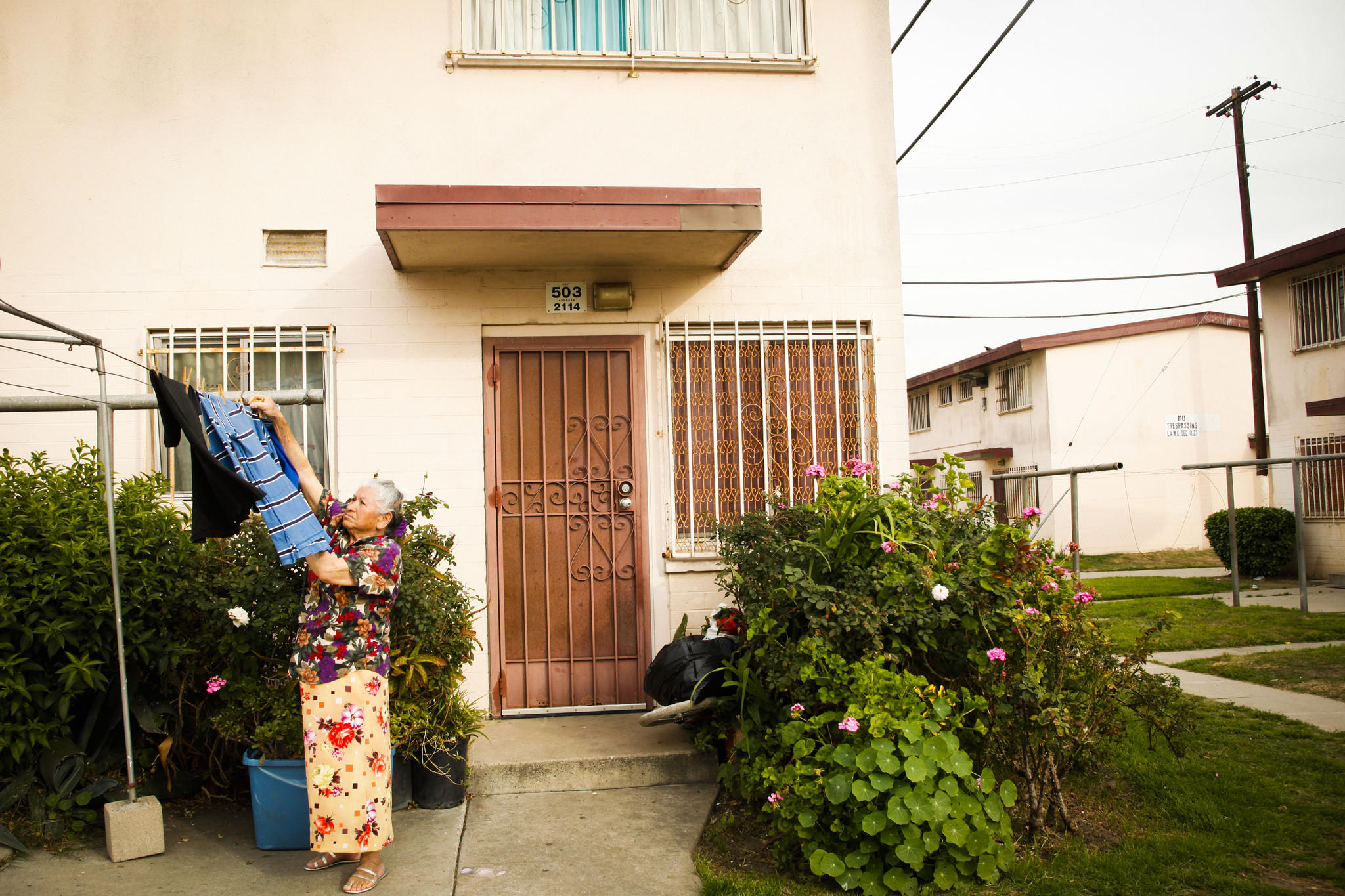 A resident hangs laundry outside of a residence in the Jordan Downs housing project in Watts.
