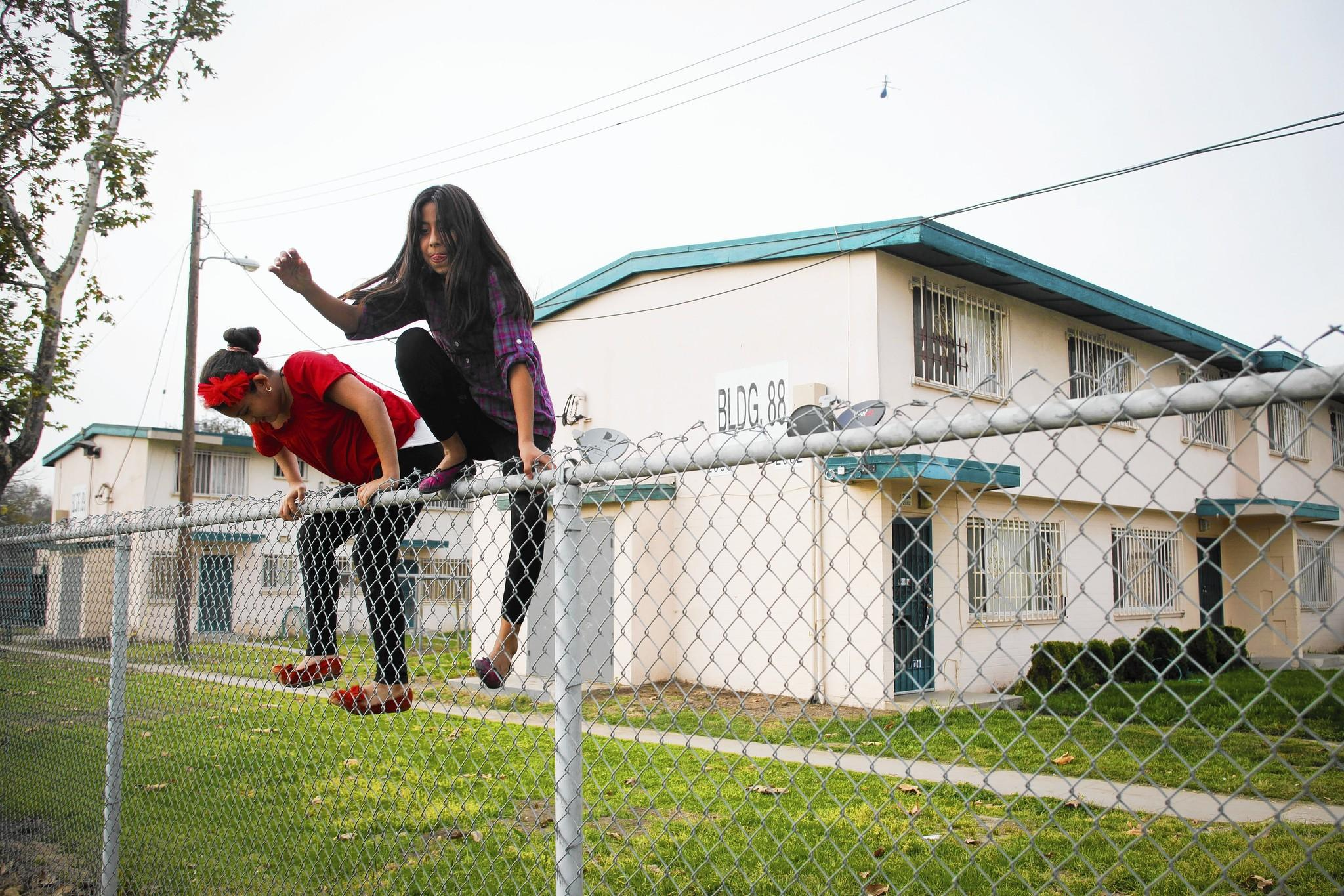 Jasmine Bermejo, left, and Rosario Gomez race each other over fences in Jordan Downs, one of the oldest housing projects in Los Angeles. The city's revitalization plan hinged on a $30-million federal grant that would have been used to leverage other funds.